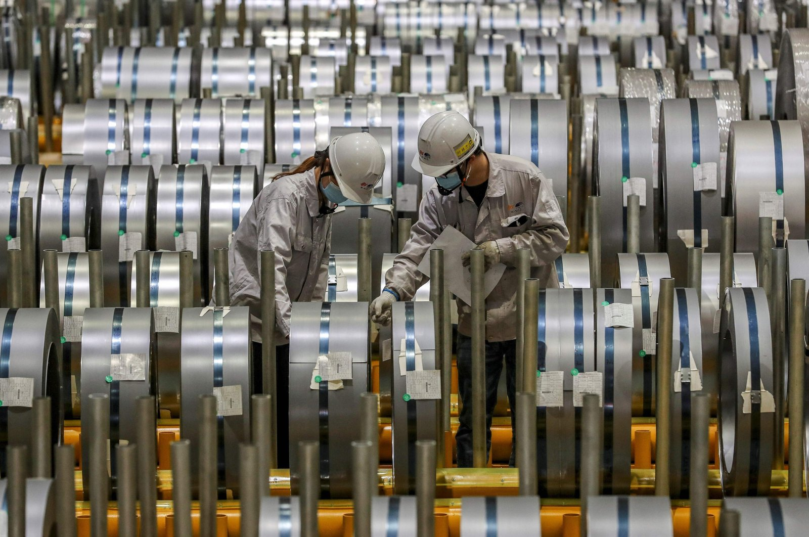 Workers checking rolls of sheet aluminium at a factory in Wuhan, central Hubei province, China, May 8, 2021. (AFP Photo)