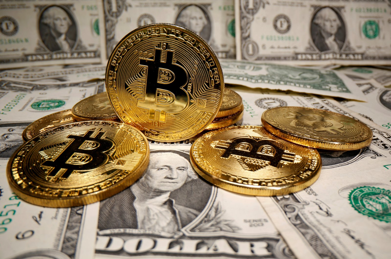 Representations of the cryptocurrency Bitcoin are placed on U.S. dollar banknotes in this illustration taken on May 26, 2020. (Reuters Photo)