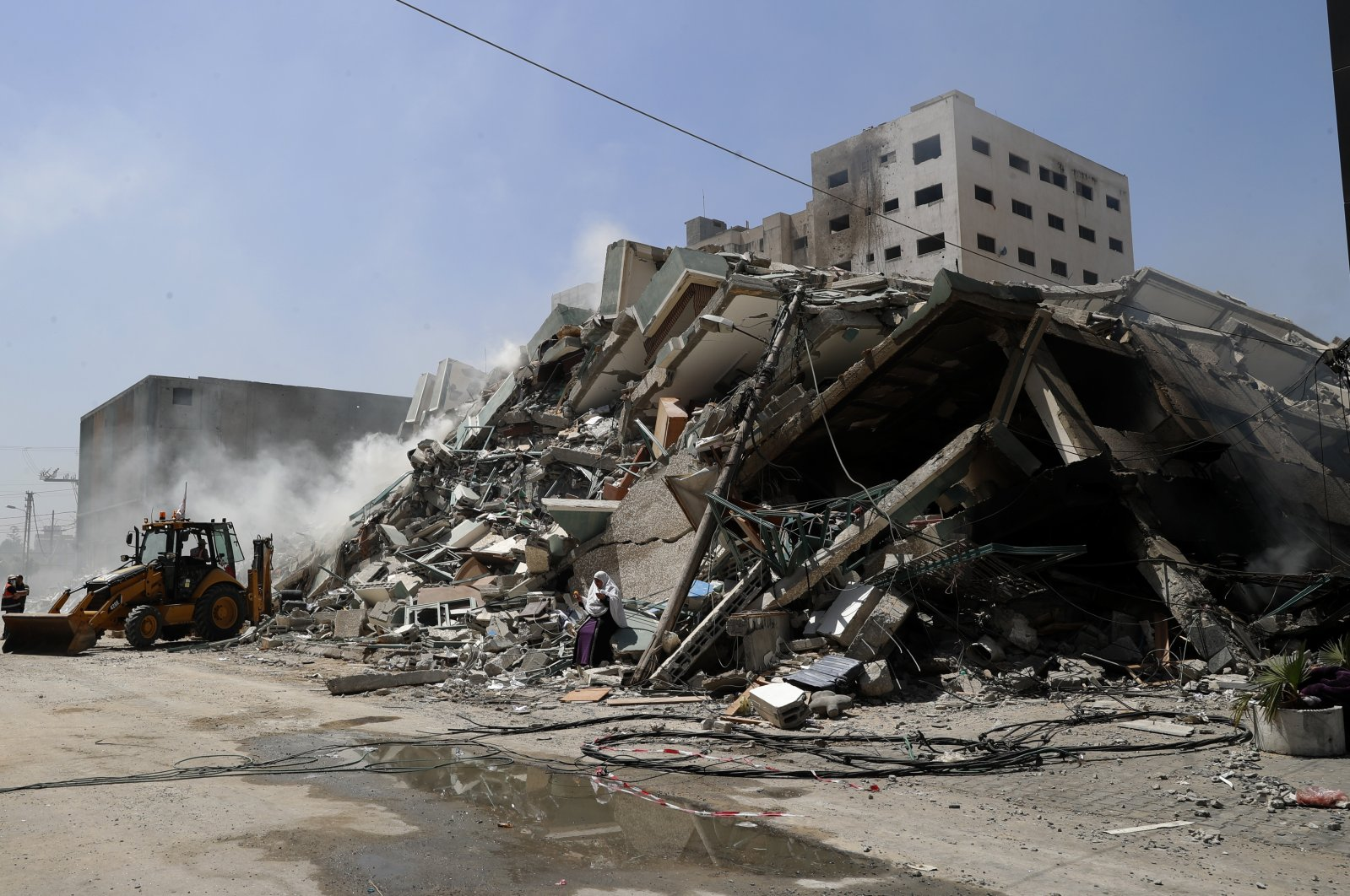 Workers clear the rubble of a building that was destroyed by an Israeli airstrike on Saturday, that housed The Associated Press, broadcaster Al-Jazeera and other media outlets, in Gaza City, Palestine, May 16, 2021. (AP Photo)