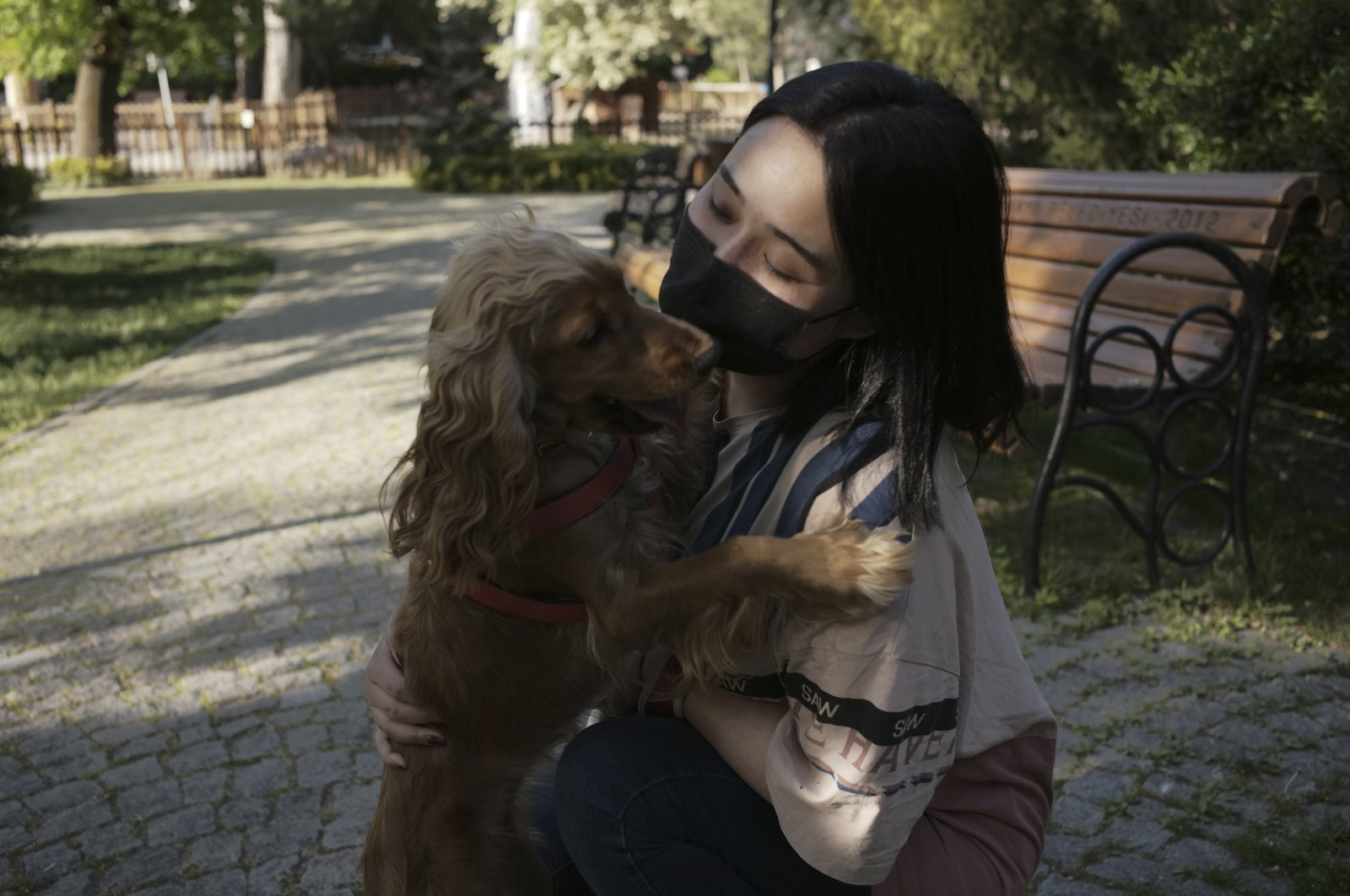 A woman wearing a protective mask, against the spread of the coronavirus, hugs her dog at a park during a lockdown, Ankara, Turkey, May 12, 2021. (AP Photo)