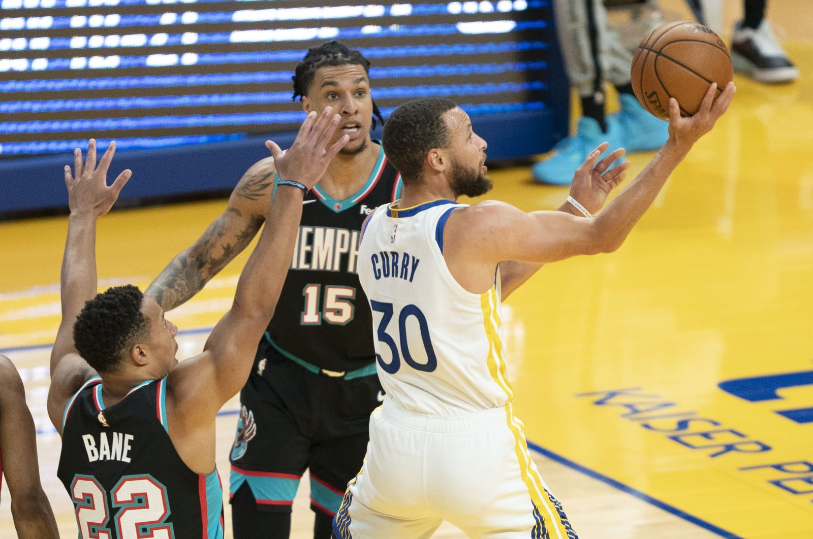 Golden State Warriors guard Stephen Curry (R) shoots against Memphis Grizzlies guard Desmond Bane (L) and forward Brandon Clarke (C) during an NBA match at Chase Center, San Francisco, California, U.S., May 16, 2021. (AFP Photo)