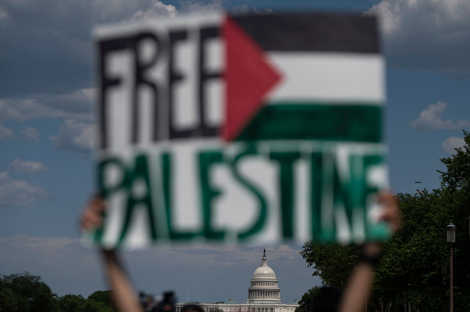 An activist holds up a sign with the U.S. Capitol in the background, in support of Palestine, near the Washington Monument in Washington, D.C., U.S., May 15, 2021. (AFP Photo)