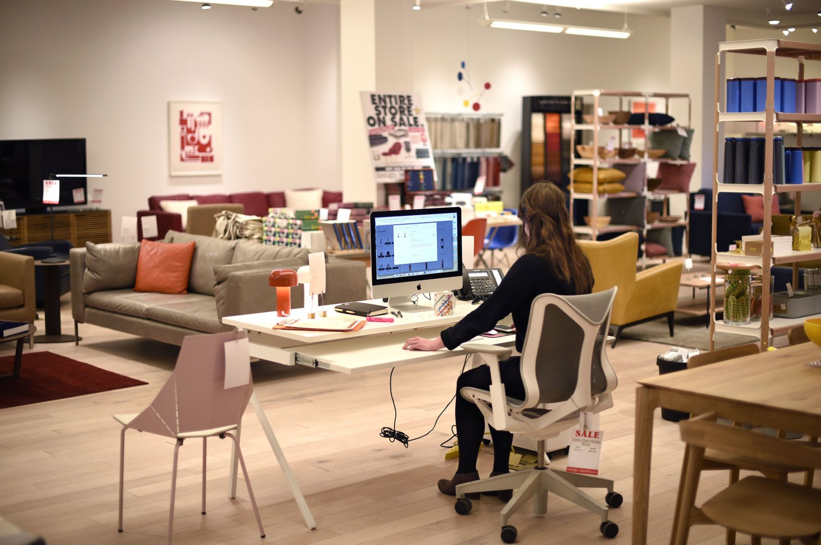 An employee works at her computer in a home and office furniture and accessory store in Santa Fe, New Mexico, U.S., Jan. 14, 2020. (Getty Images)