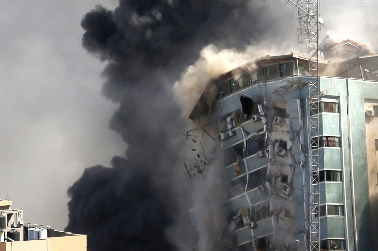 The building housing the offices of The Associated Press and other media in Gaza City collapses after it was hit by an Israeli airstrike, Palestine, May 15, 2021. (AP Photo)