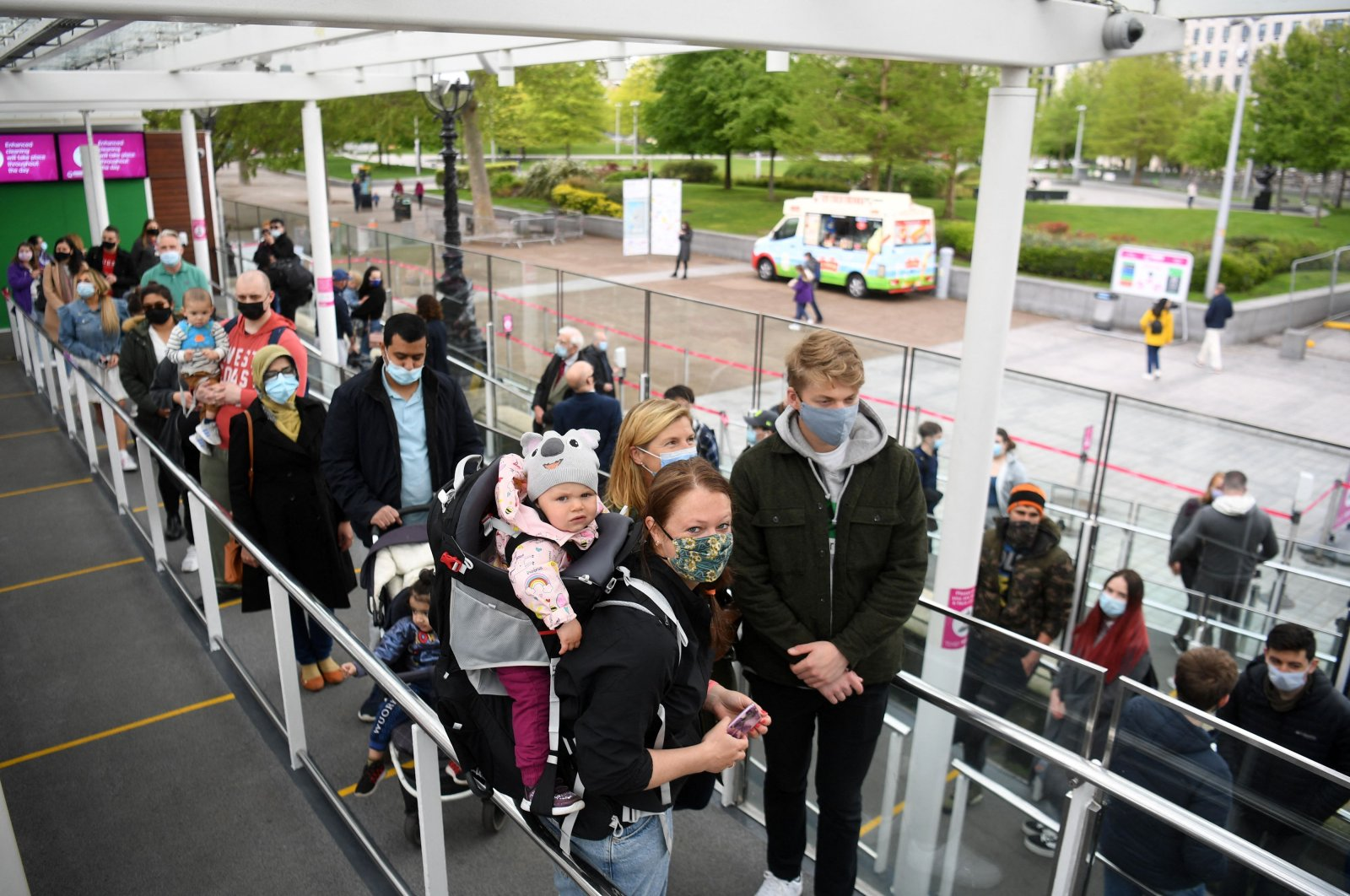 Customers wearing face coverings queue to board a pod on the re-opened London Eye tourist attraction in London as COVID-19 lockdown restrictions ease across the U.K., May 17, 2021. (AFP Photo)