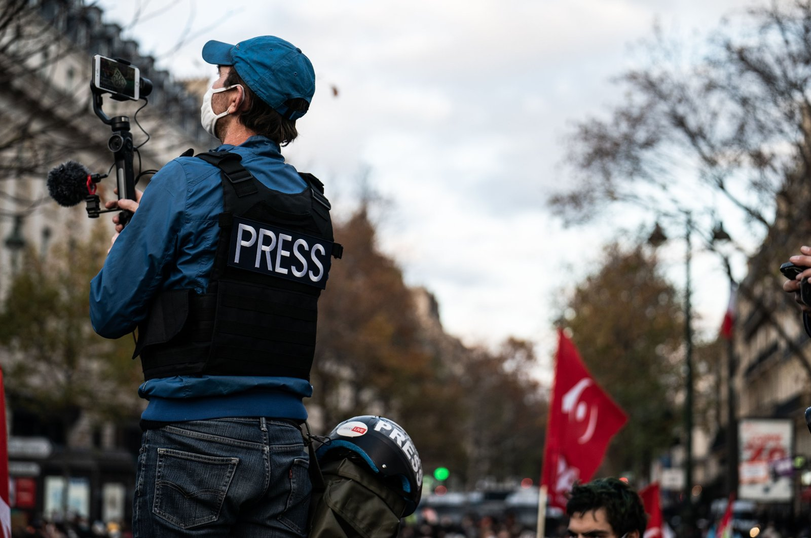 """A journalist wearing a vest and a helmet with the message """"press"""" records the demonstration on video, Paris, Nov. 21, 2020. (Reuters Photo)"""