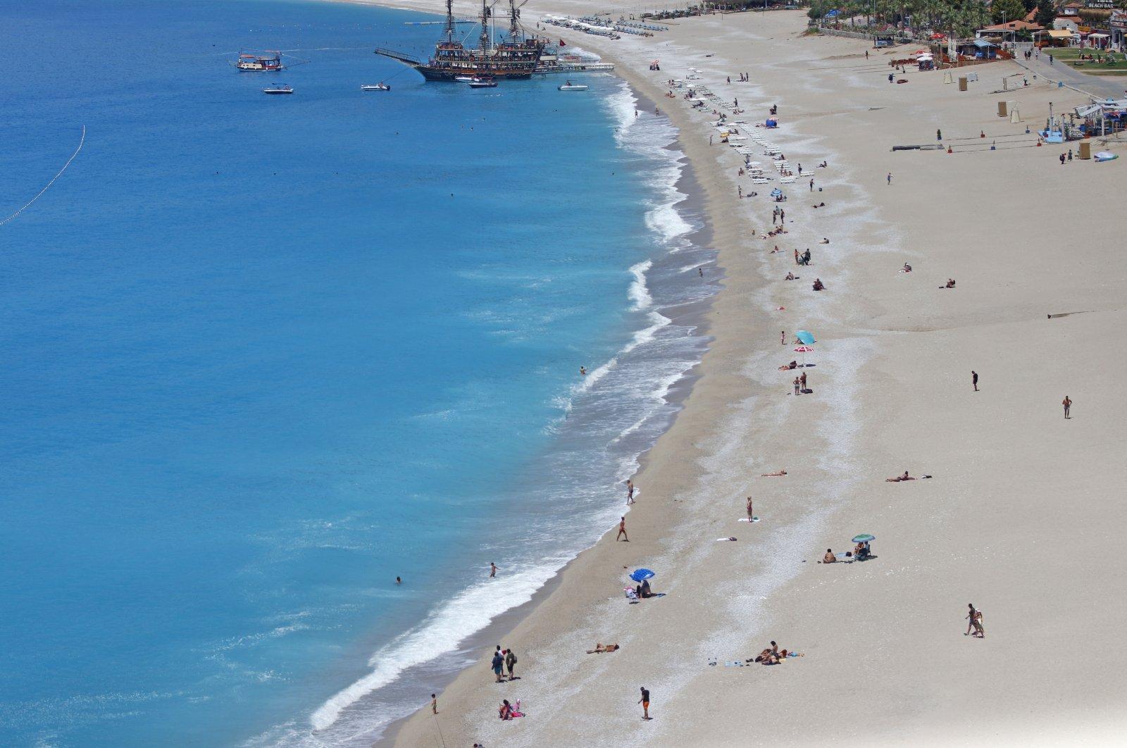 People are seen on a beachin Fethiye, Muğla province, southwestern Turkey, May 17, 2021.