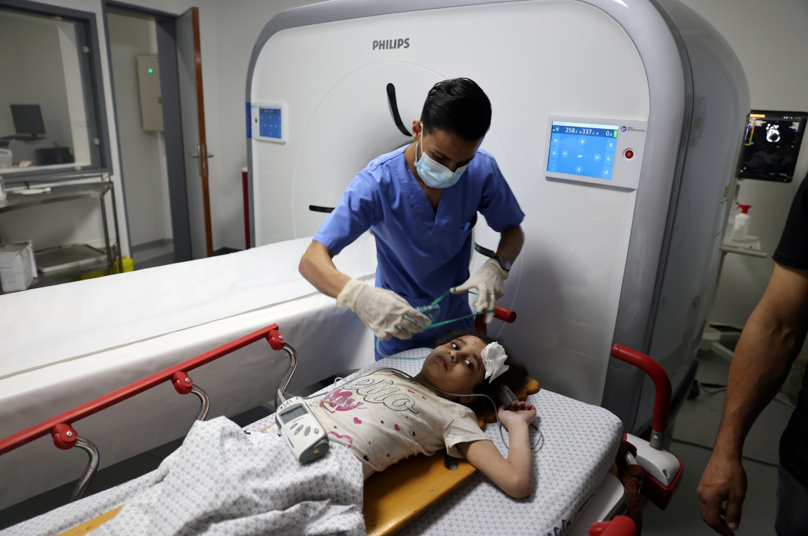 A Palestinian girl is treated by a medic at a hospital after being pulled from the rubble of a building amidst Israeli airstrikes, in Gaza City, Palestine, May 16, 2021. (Reuters Photo)