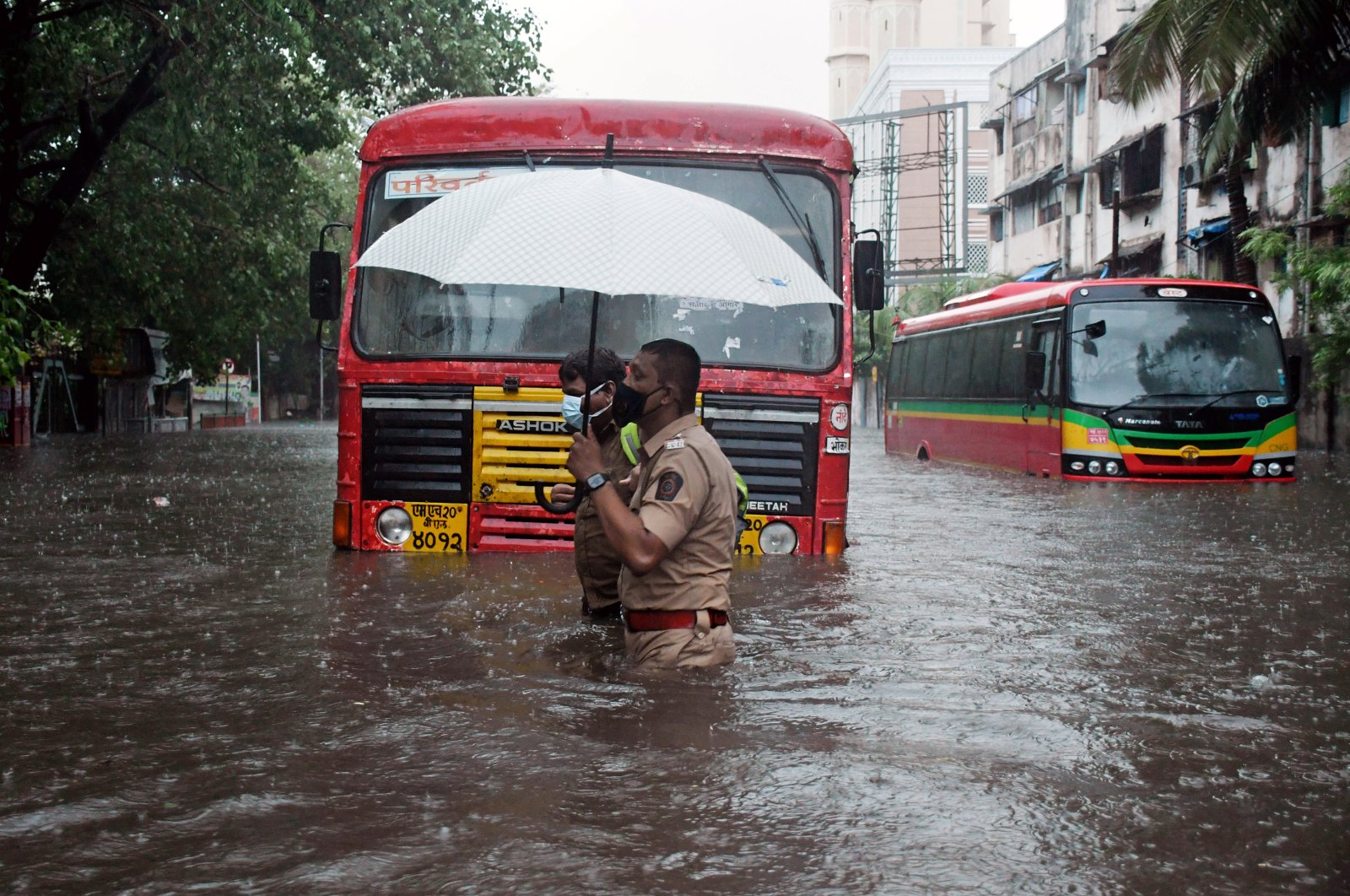 An Indian police officer helps a driver cross a street flooded by heavy rain caused by cyclone Tauktae in Mumbai, India, May 17, 2021. (EPA Photo)