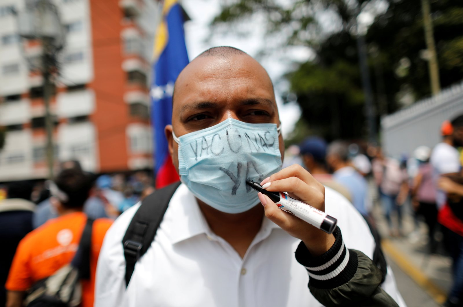"""A person writes """"Vaccines, now!"""" on the face mask of a health care worker during a protest demanding vaccinations against COVID-19, in Caracas, Venezuela, April 17, 2021. (REUTERS Photo)"""