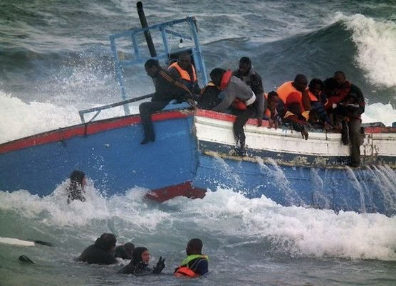 Italian Coast Guard scuba divers, seen bottom left, rescue migrants in Pantelleria, Italy, April 13, 2011. (Italian Coast Guard via AP)