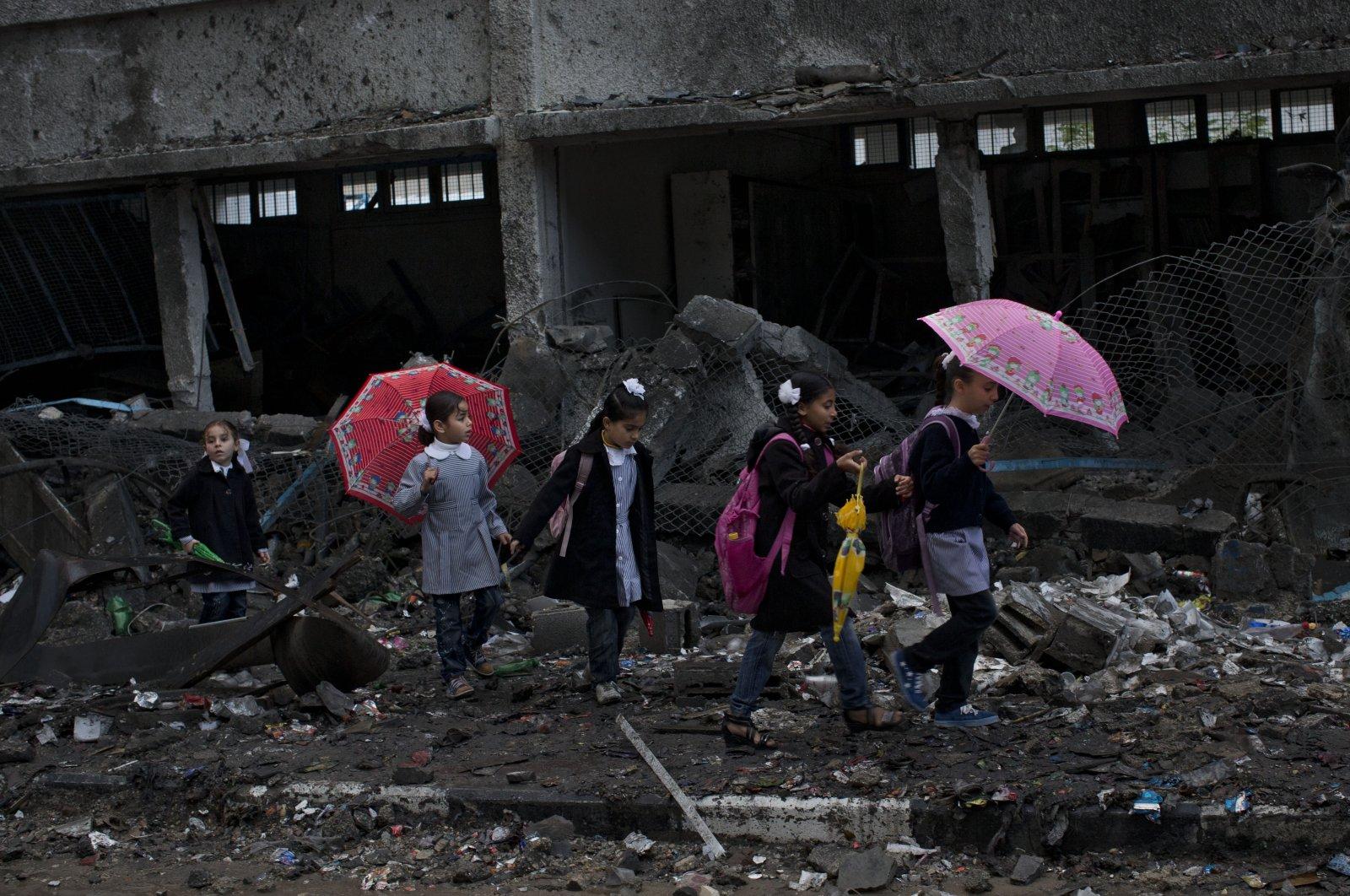 Palestinian schoolchildren walk among the debris of a damaged school targeted by Israeli attacks in Gaza City, Palestine, Nov. 24, 2012. (AP Photo)