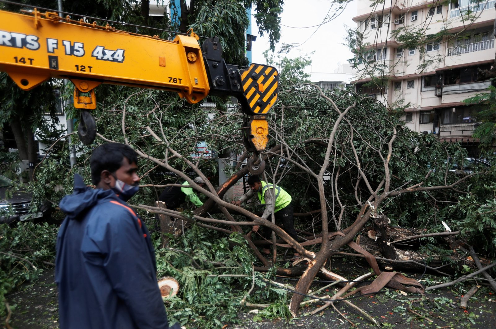 People attempt to remove uprooted trees from the entrance of a residential building after strong winds caused by Cyclone Tauktae, in Mumbai, India, May 18, 2021. (Reuters Photo)