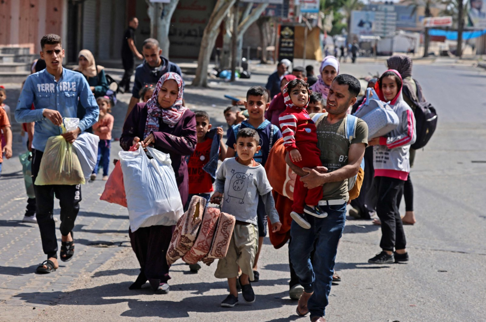 Palestinians carry some of their belongings as they flee Israeli air and artillery strikes in Beit Hanun in the northern Gaza Strip, Palestine, on May 14, 2021. (AFP Photo)
