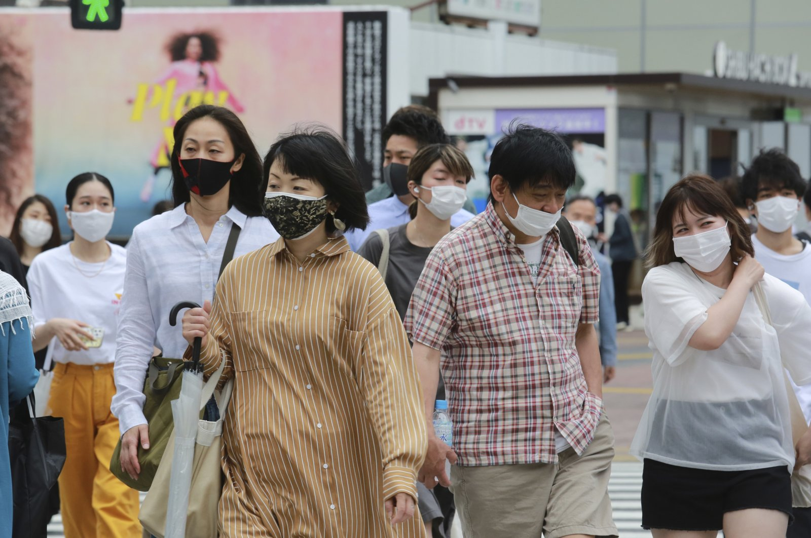 People wearing face masks to protect against the spread of the coronavirus walk on a street in Tokyo, Japan, May 18, 2021. (AP Photo)