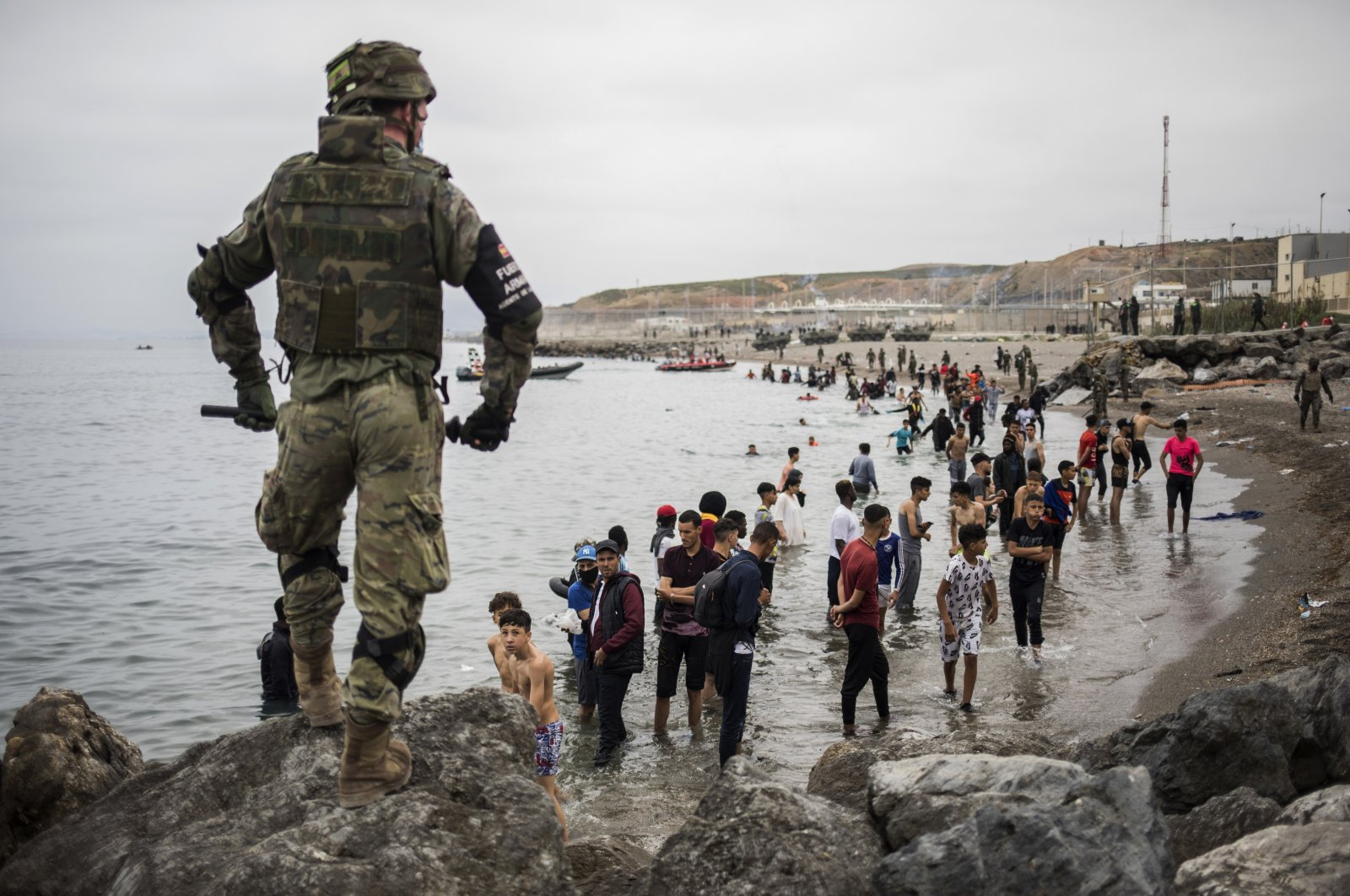 People mainly from Morocco stand on the shore as Spanish Army cordon off the area at the border of Morocco and Spain, at the Spanish enclave of Ceuta, on Tuesday, May 18, 2021. (AP Photo)