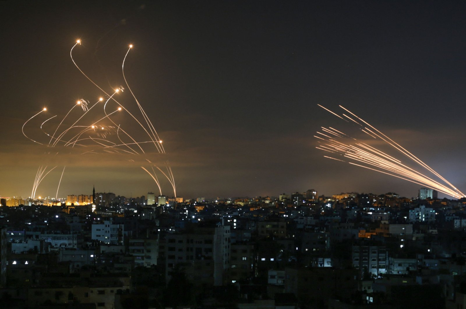 The Israeli Iron Dome missile defence system (L) intercepts rockets (R) fired by the Hamas towards southern Israel from Beit Lahia in the northern Gaza Strip as seen in the sky above the Gaza Strip overnight on May 14, 2021. (AFP Photo)