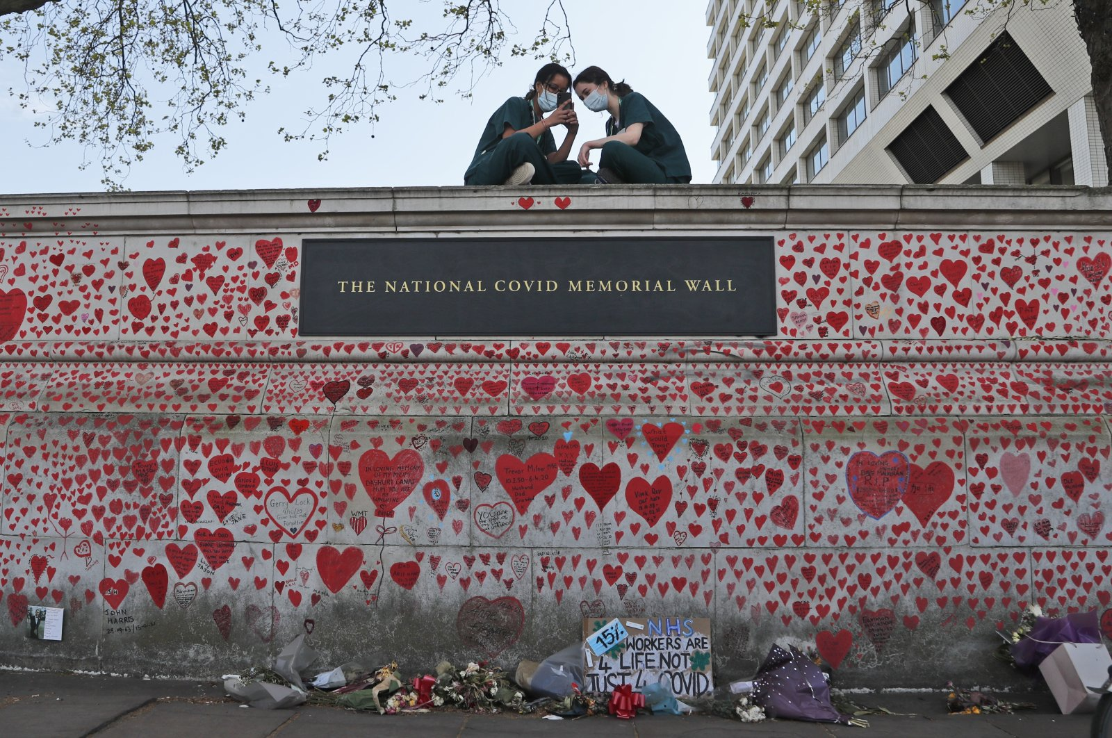 Nurses from the nearby St Thomas' hospital sit atop the National Covid Memorial Wall in London, U.K., Tuesday, April 27, 2021. (AP Photo)