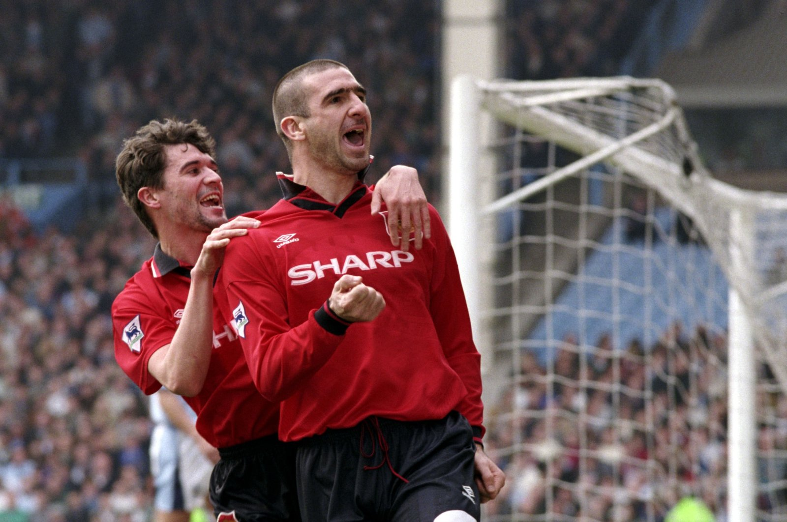 Manchester United's Eric Cantona (R) celebrates his goal with teammate Roy Keane during the Premier League football match between Manchester City and Manchester United at the Maine Road in Manchester, England, April 6, 1996. (Action Images/Darren Walsh via Reuters)