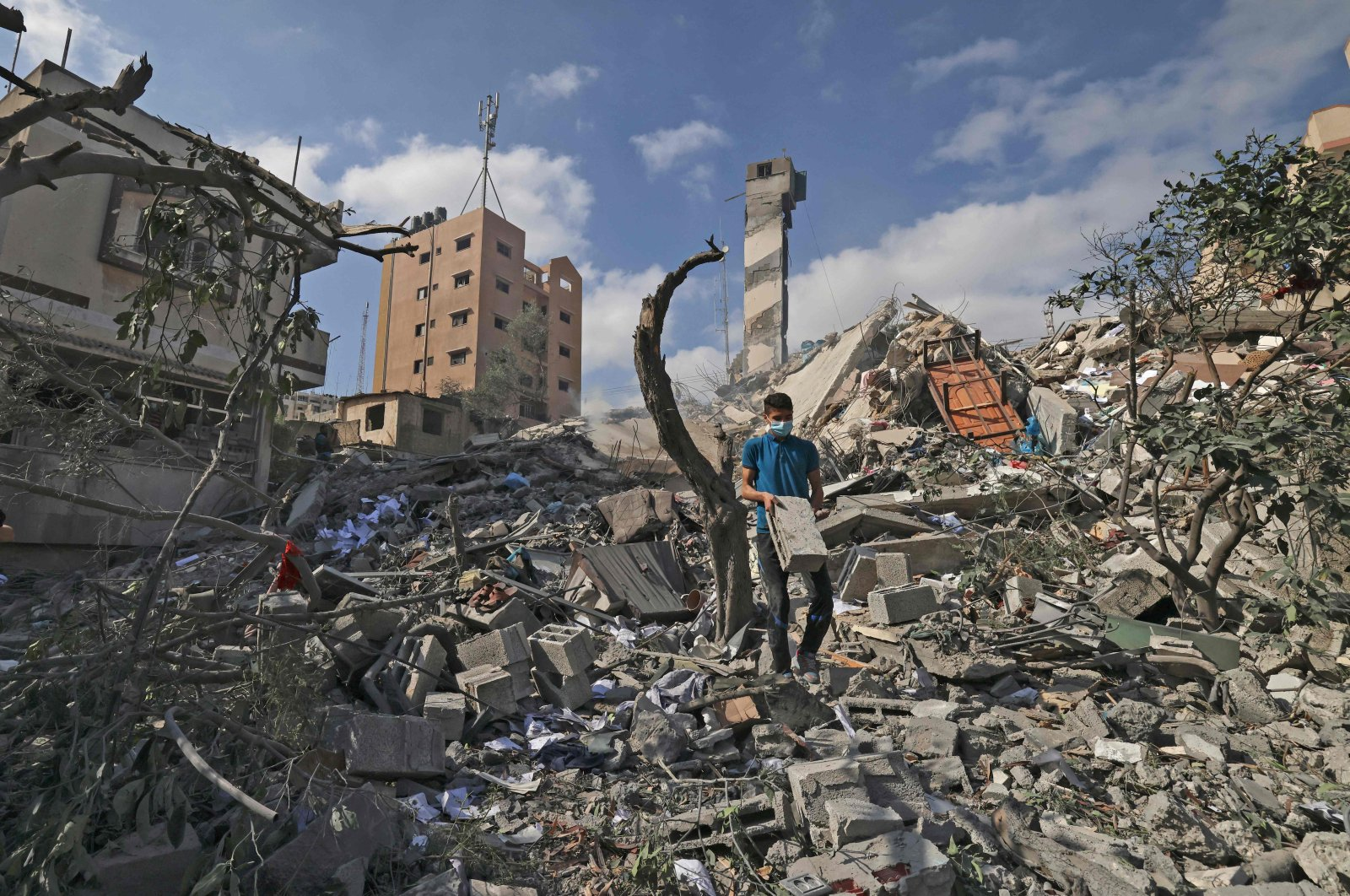 A Palestinian youth looks for salvageable items amid the rubbe of the Kuhail building which was destroyed in an early morning Israeli airstrike on Gaza City on May 18, 2021. (AFP Photo)
