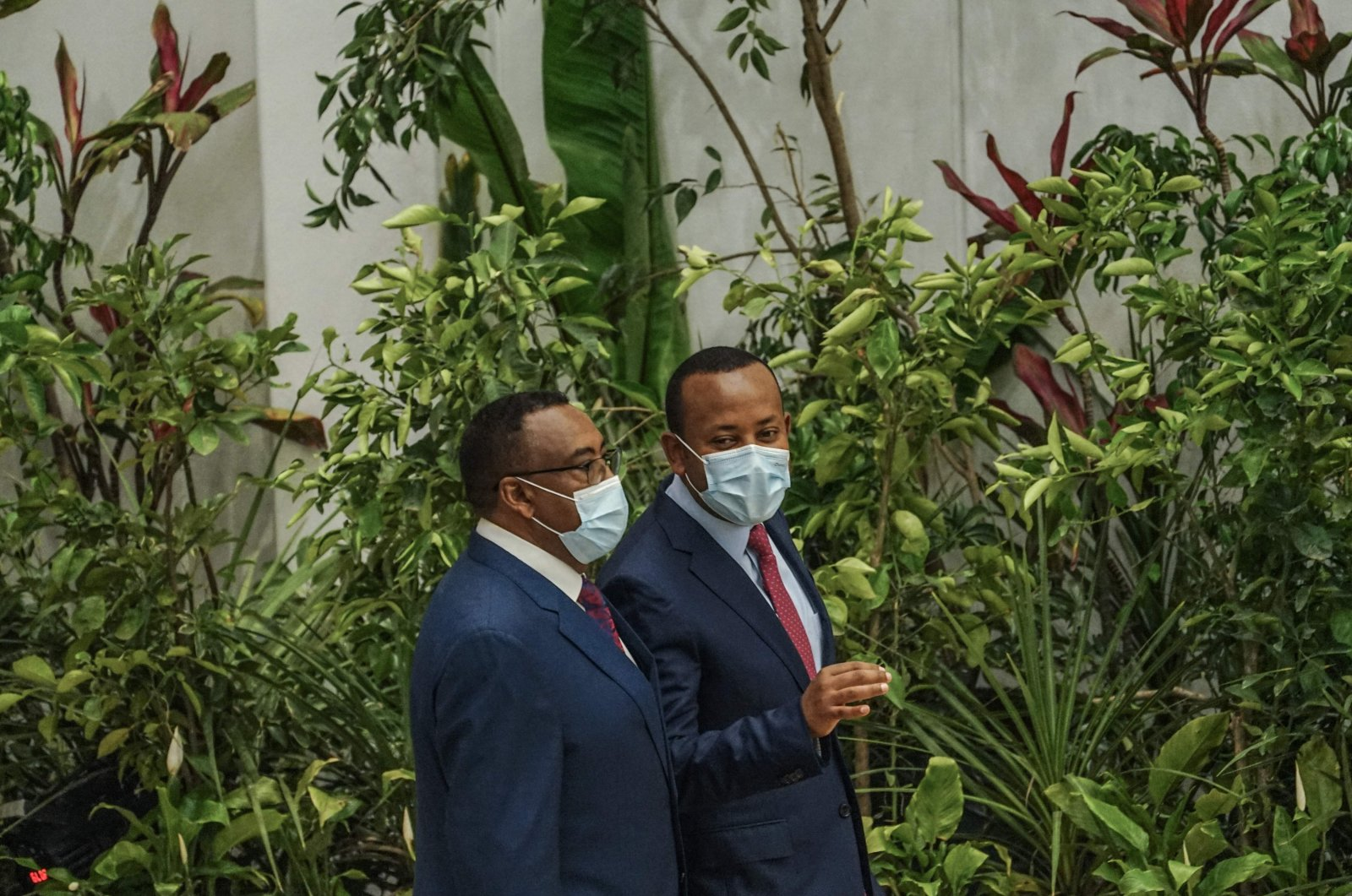 """Ethiopian Prime Minister Abiy Ahmed (R) speaks with Deputy Prime Minister Demeke Mekonen during the launch of his """"Green Legacy"""" initiative, where a hall of the Prime Minister's office temporarily transformed into a green garden, Addis Ababa, Ethiopia, May 18, 2021.  (AFP Photo)"""