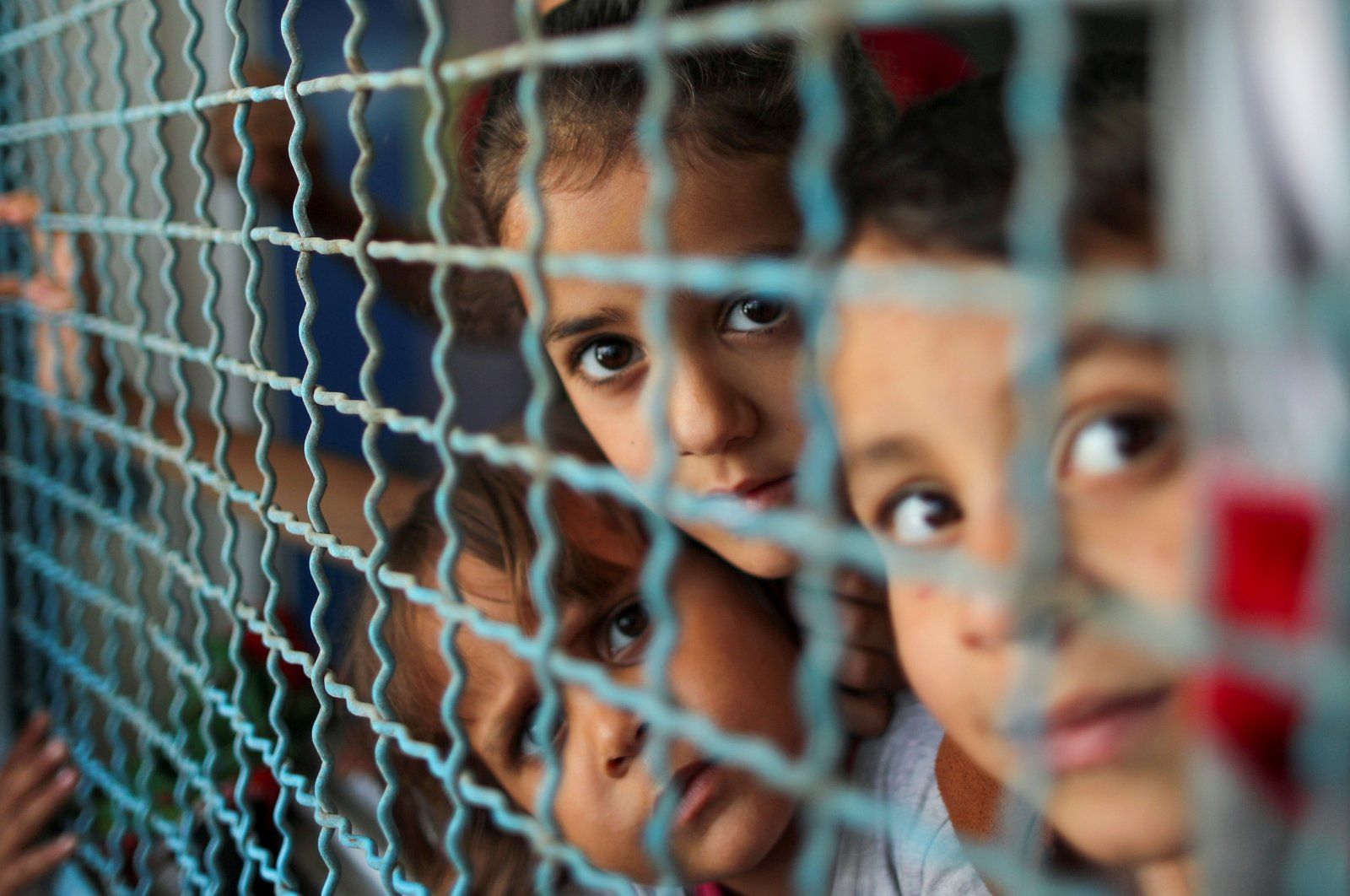 Palestinian children, who fled their homes due to Israeli air and artillery strikes, look through a window fence at a United Nations-run school where they take refuge, in Gaza City, Palestine, May 18, 2021.  (Reuters Photo)