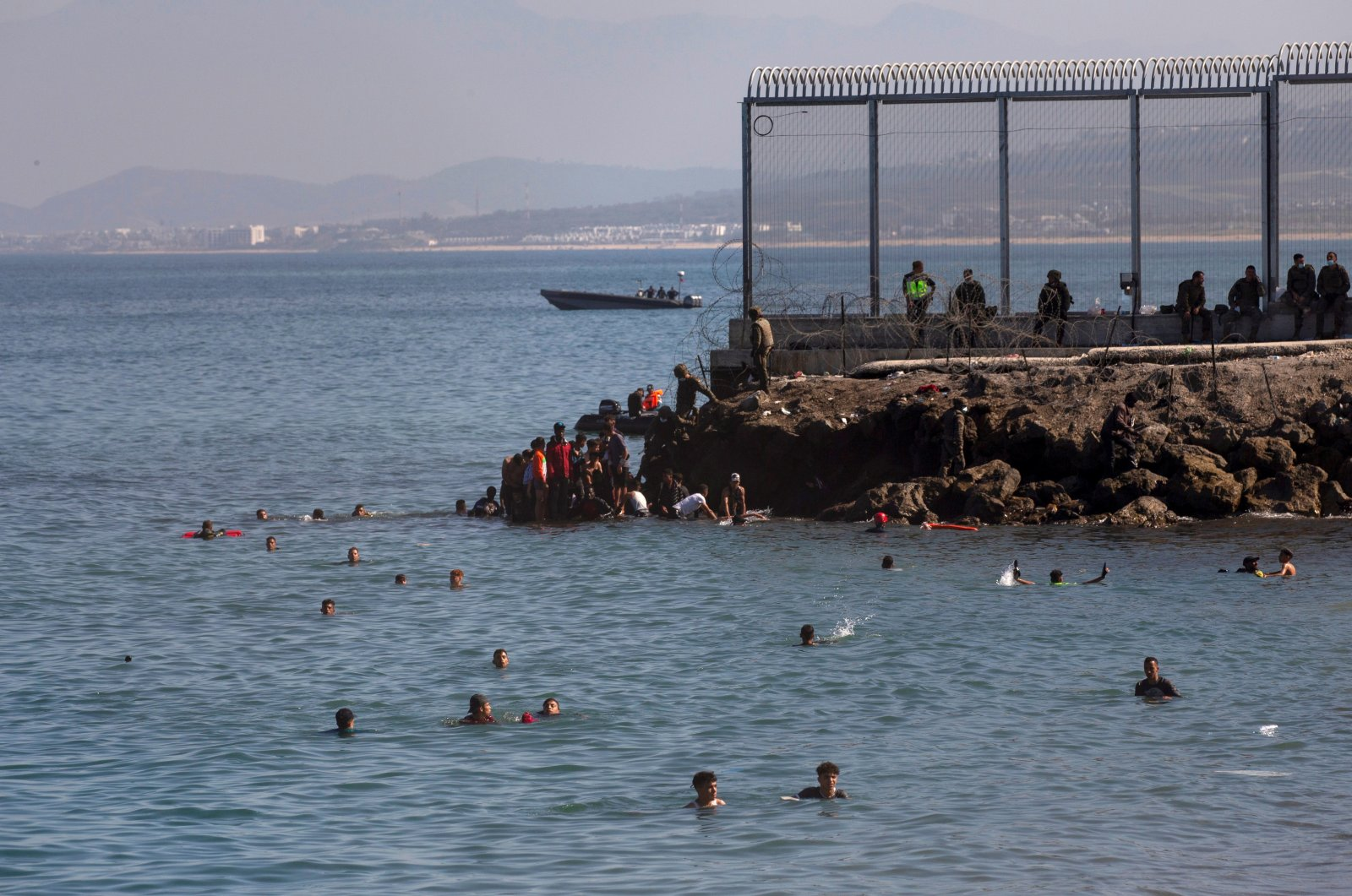 Migrants swim to cross the border of Tarajal in Ceuta, Spain. On the night of 18 May, a total of 5,000 Moroccan nationals entered the Spanish city of Ceuta, located on the North African coast, May 18, 2021. (EPA / BRAIS LORENZO)