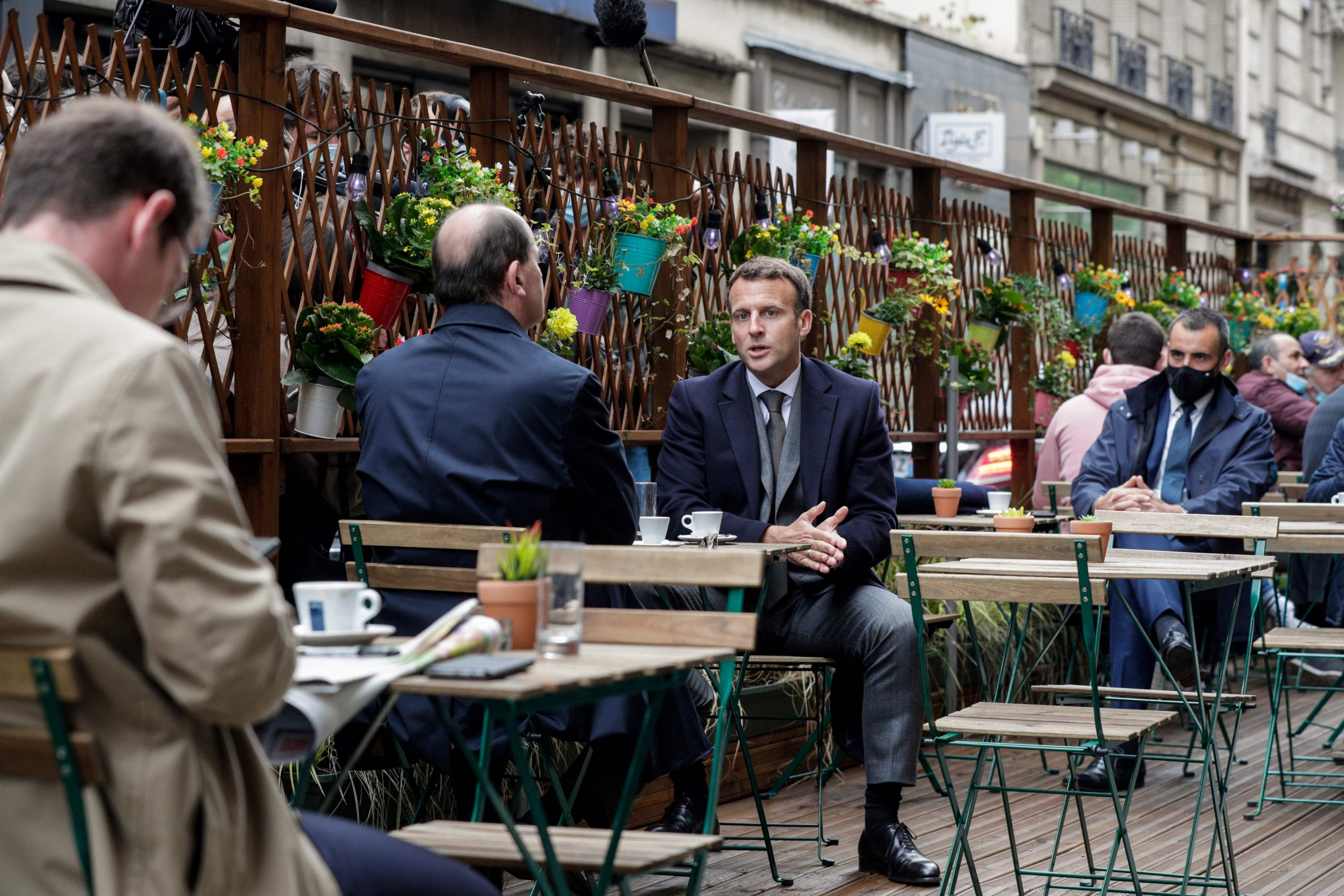 French President Emmanuel Macron (R) and French Prime Minister Jean Castex (L) are having coffees at a cafe terrace in Paris on May 19, 2021. (AFP Photo)
