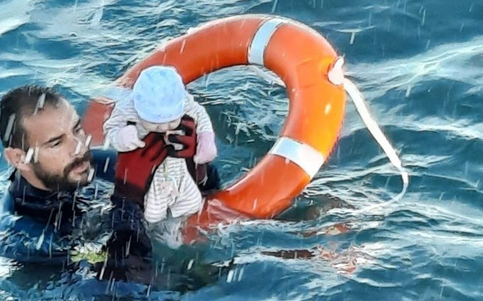 A member of the Spanish Civil Guard rescues a baby in Ceuta after migrants arrive in the region, Spain, May 18, 2021. (Photo courtesy of Guardia Civil/Twitter/@guardiacivil)