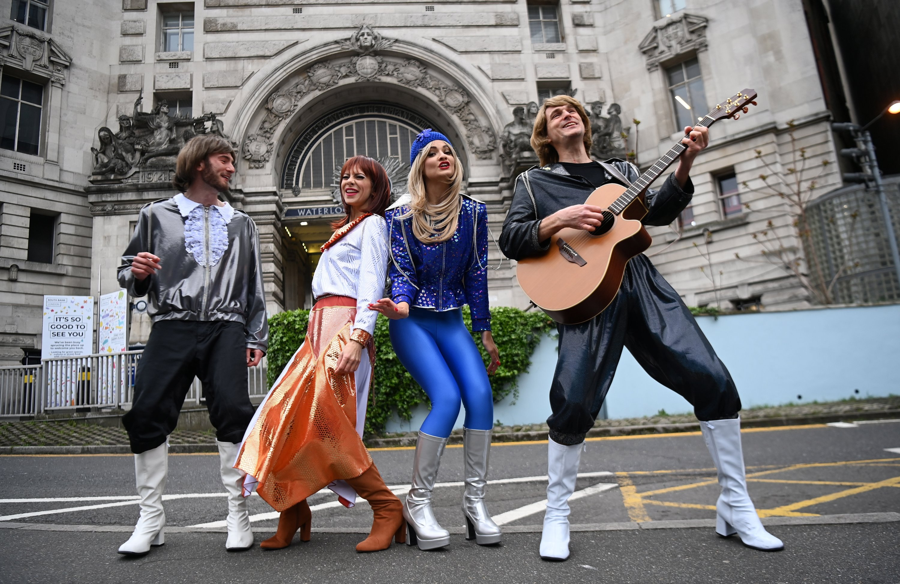 The cast of 'Abba Mania' poses outside Waterloo Station in London, Britain, May 14, 2021. (EPA/ANDY RAIN HANDOUT)