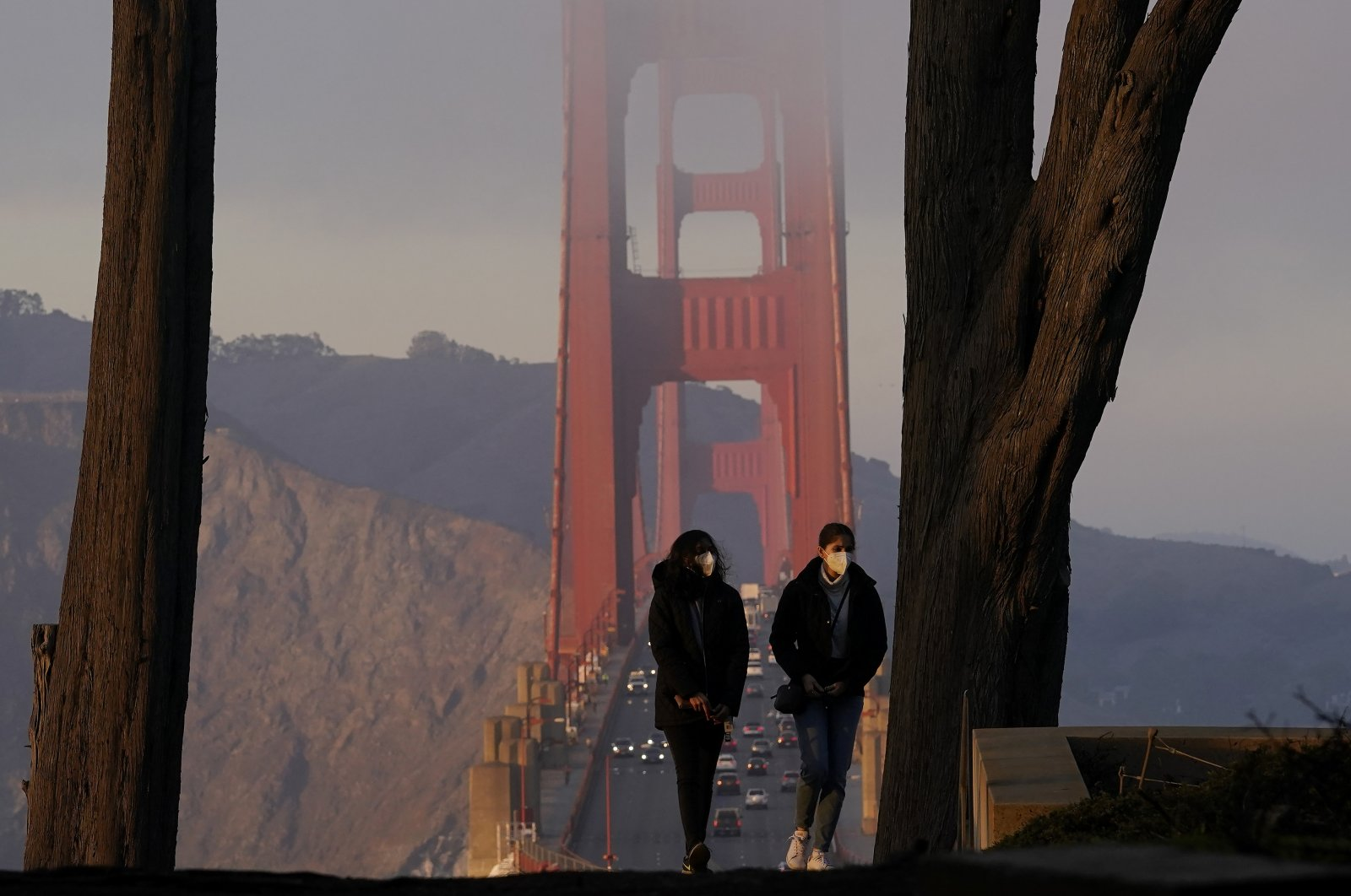 People wear face masks while walking up the stairs at the Golden Gate Overlook in front of traffic driving on the Golden Gate Bridge in San Francisco, California, Dec. 21, 2020. (AP Photo)