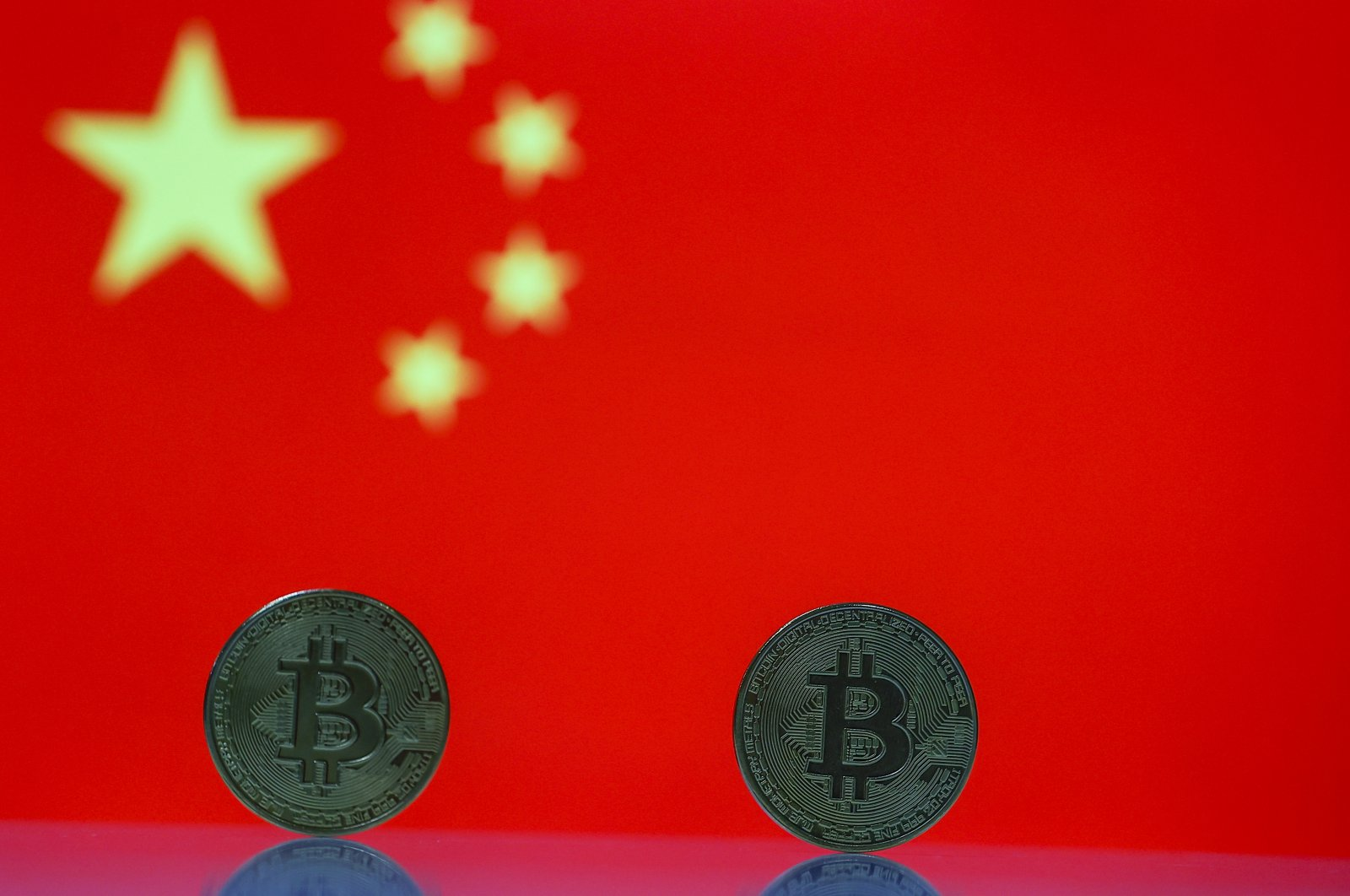 Tangible Bitcoin coins are seen in front of a Chinese flag in this illustration photo, May 18, 2021. (AA Photo)