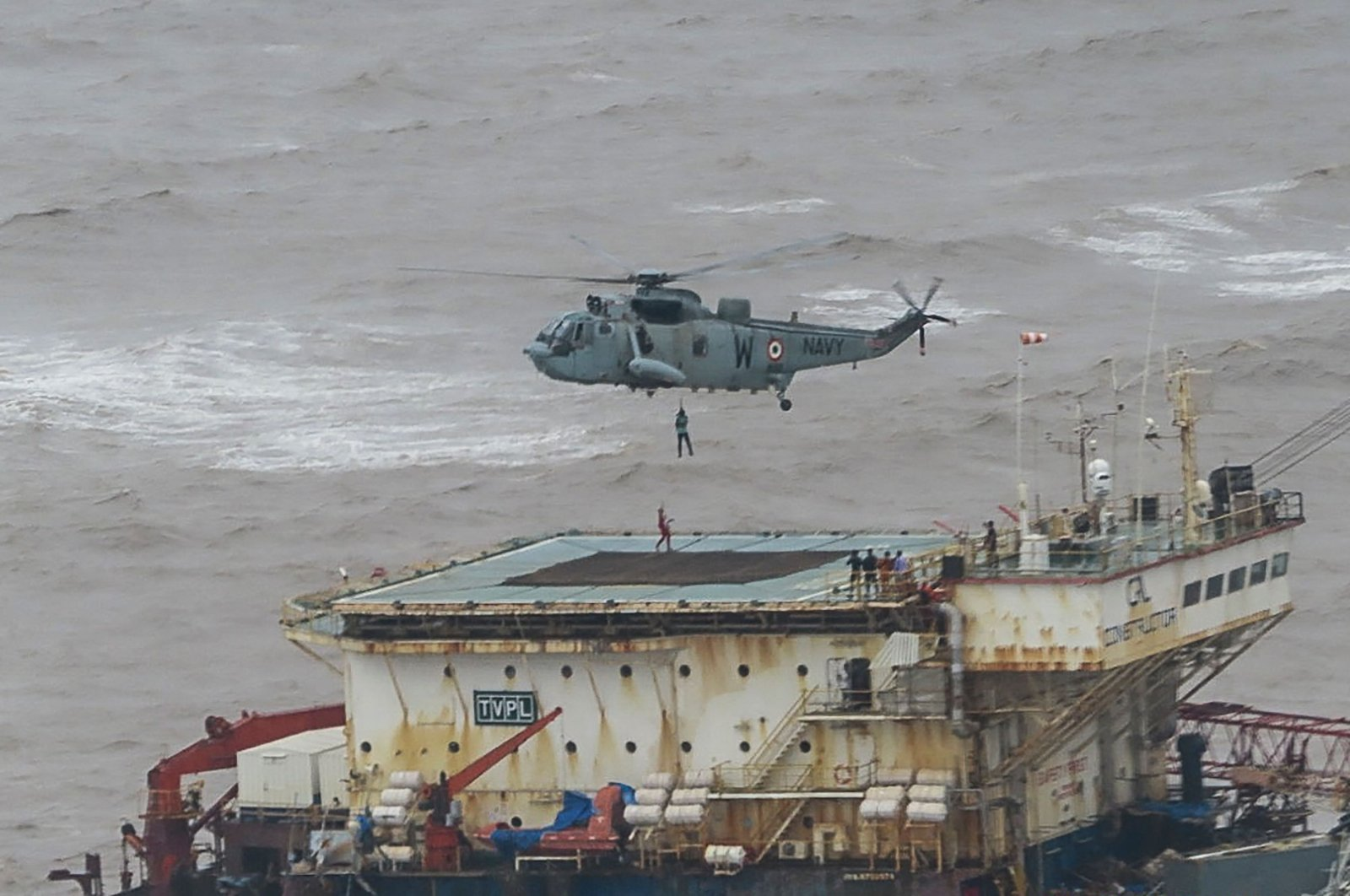 Stranded workers are airlifted by naval personnel on an Indian Navy Seaking helicopter from a barge that had gone adrift amidst heavy rain and strong winds due to Cyclone Tauktae, the Arabian Sea, May 18, 2021. (Indian Navy handout photo via AFP)