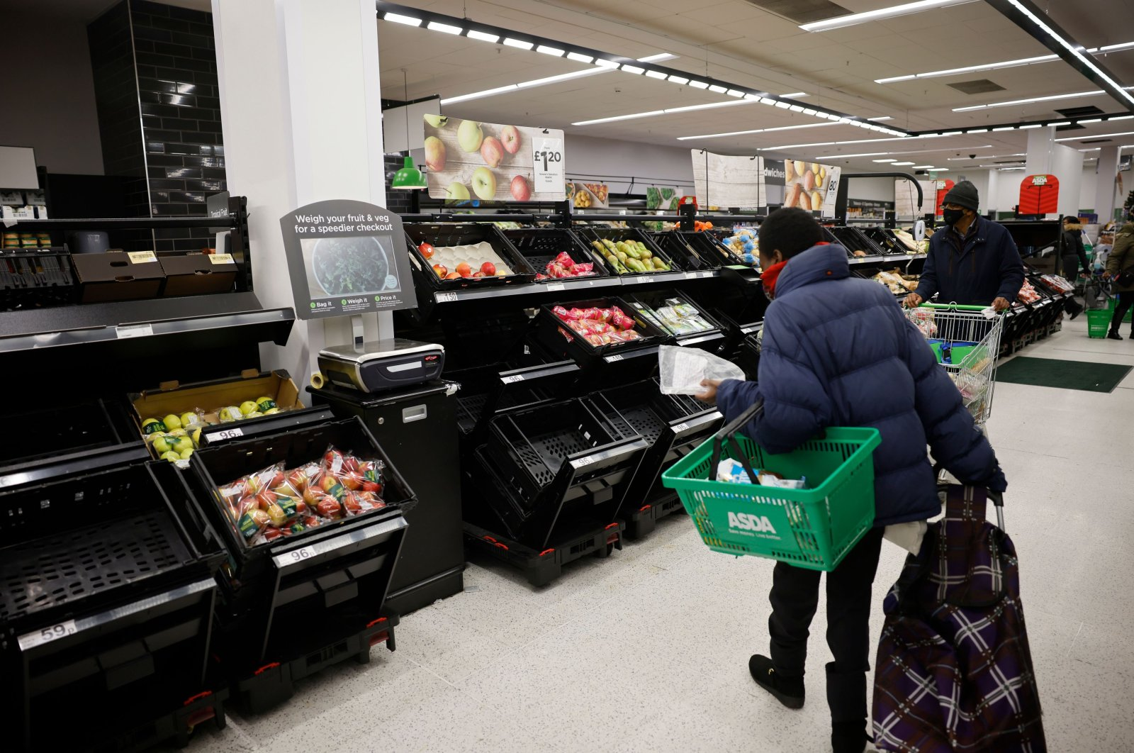 Shoppers, wearing face masks due to the COVID-19 pandemic, look at empty fruit and vegetable bins inside an ASDA supermarket in Walthamstow, northeast London, Dec. 22, 2020. (AFP Photo)
