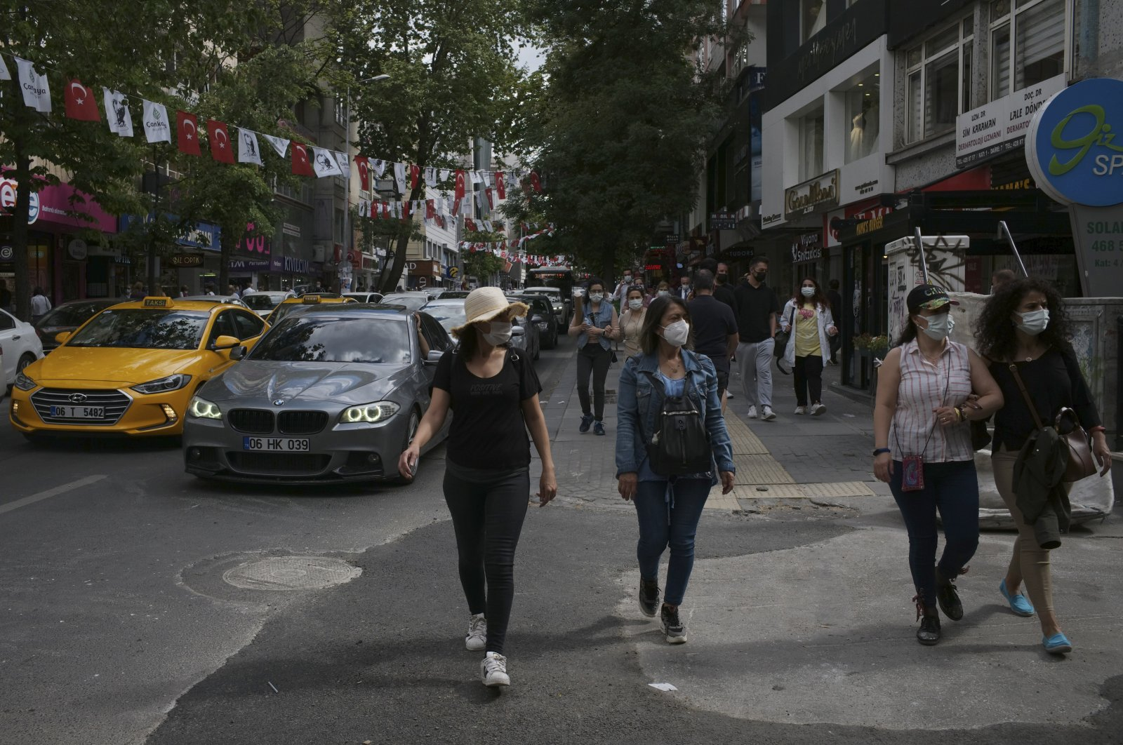 People wearing masks to help protect against the spread of the coronavirus walk near a busy street, two days after a 17-day full lockdown ended, in Ankara, Turkey, May 18, 2021. (AP Photo)