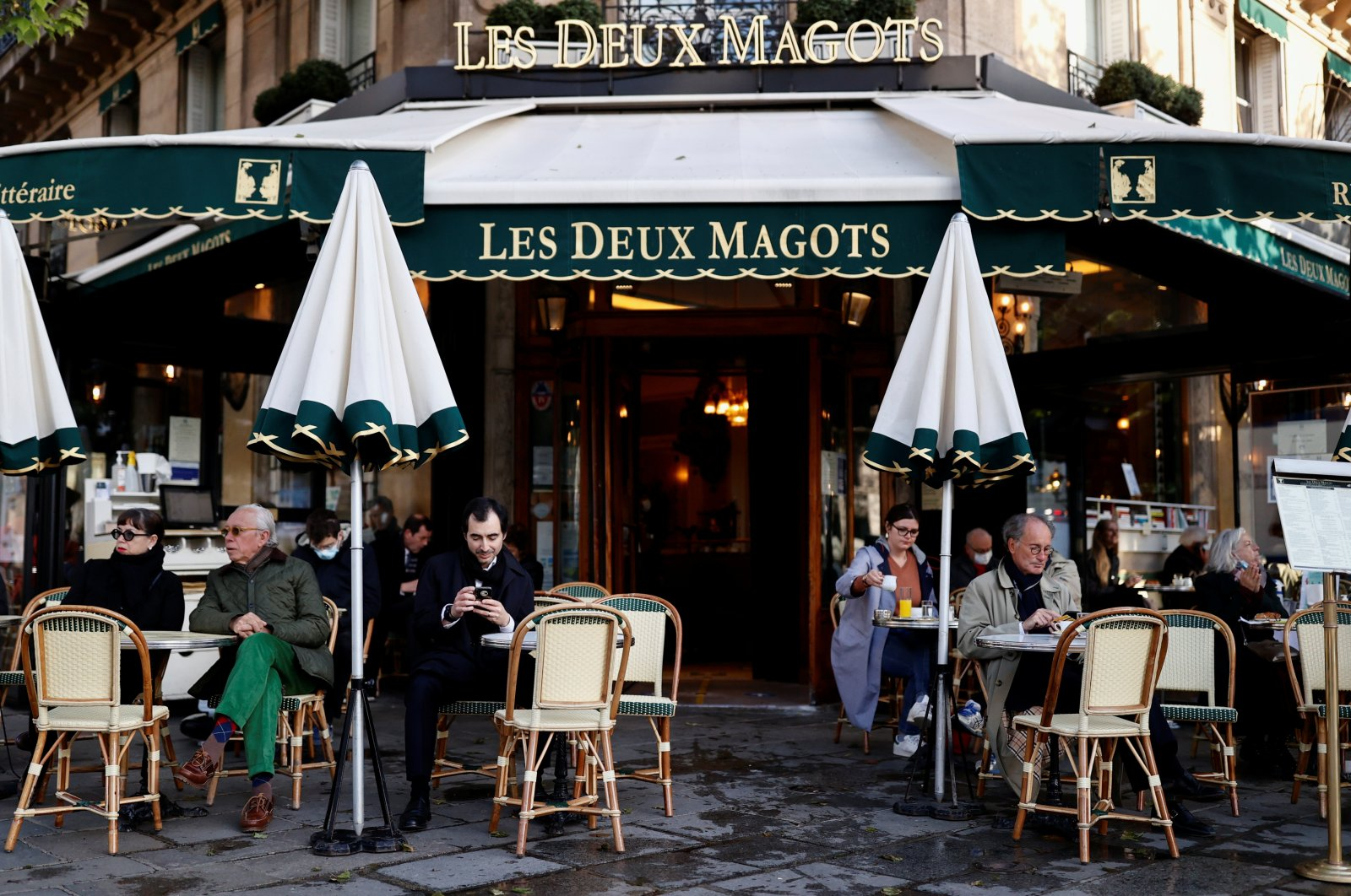 Customers sit on the terrace of the cafe and restaurant Les Deux Magots in Paris as cafes, bars and restaurants reopen after closing down for months amid the COVID-19 outbreak, Paris, France, May 19, 2021. (Reuters Photo)