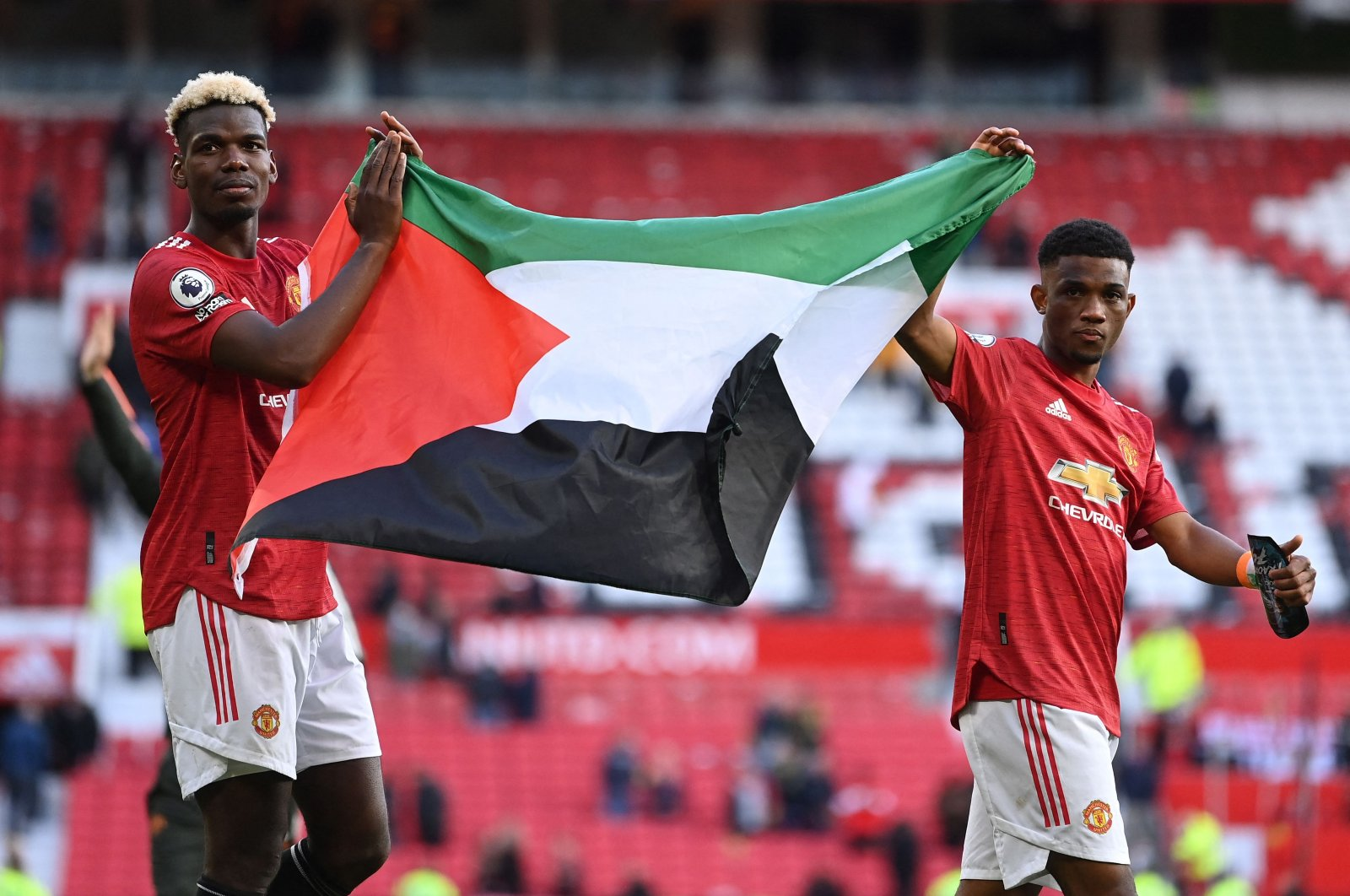 Manchester United's French midfielder Paul Pogba (L) and Manchester United's Ivorian midfielder Amad Diallo (R) display a Palestine flag at the end of their Premier League match against Fulham at the Old Trafford, Manchester, England, May 18, 2021. (AFP Photo)