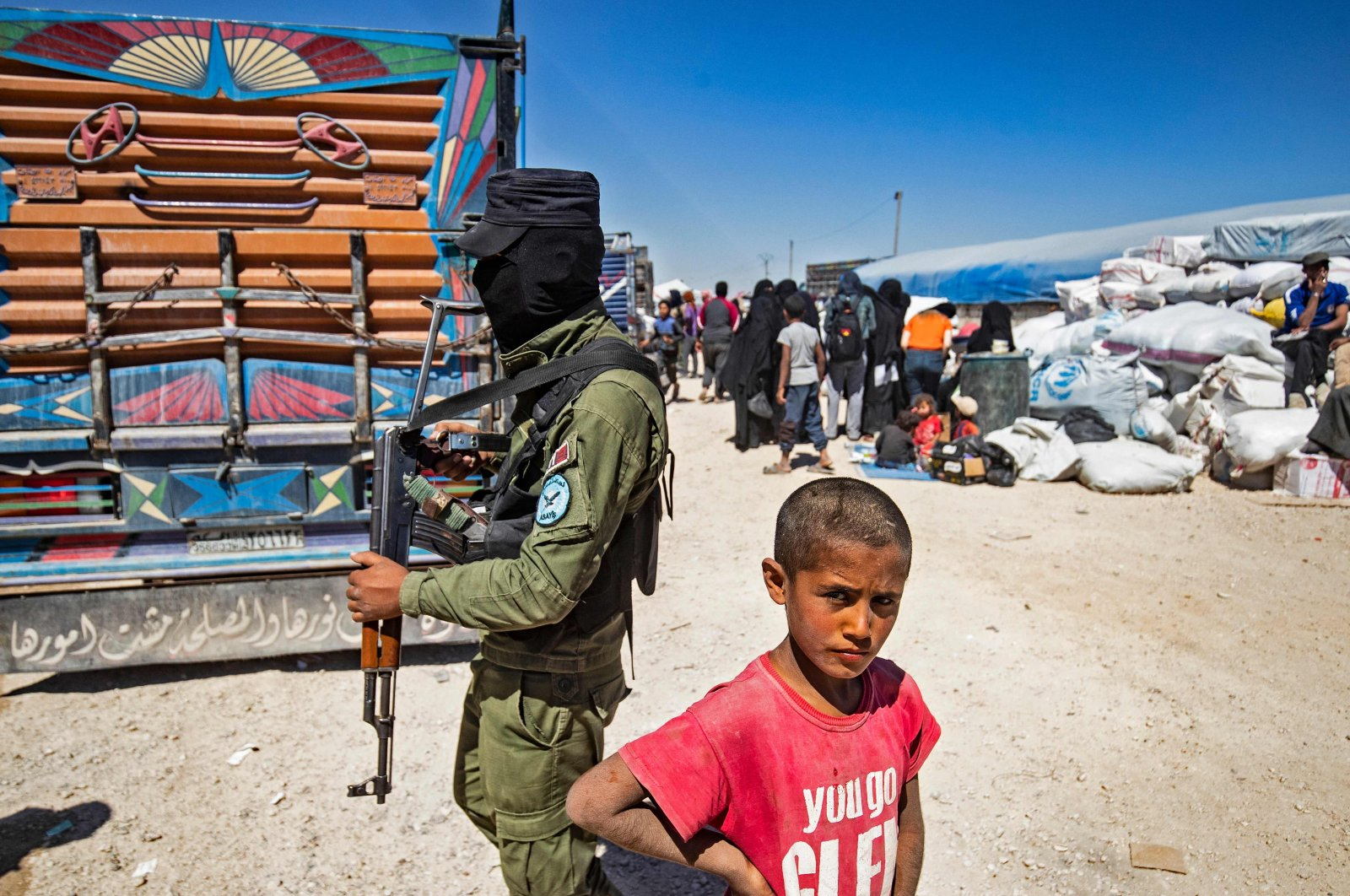 A boy stands next to a YPG terrorist amid preparations for departure as another group of Syrian families is released from the al-Hol camp in the northeastern Hassakeh governorate, Syria, on May 11, 2021. (AFP Photo)