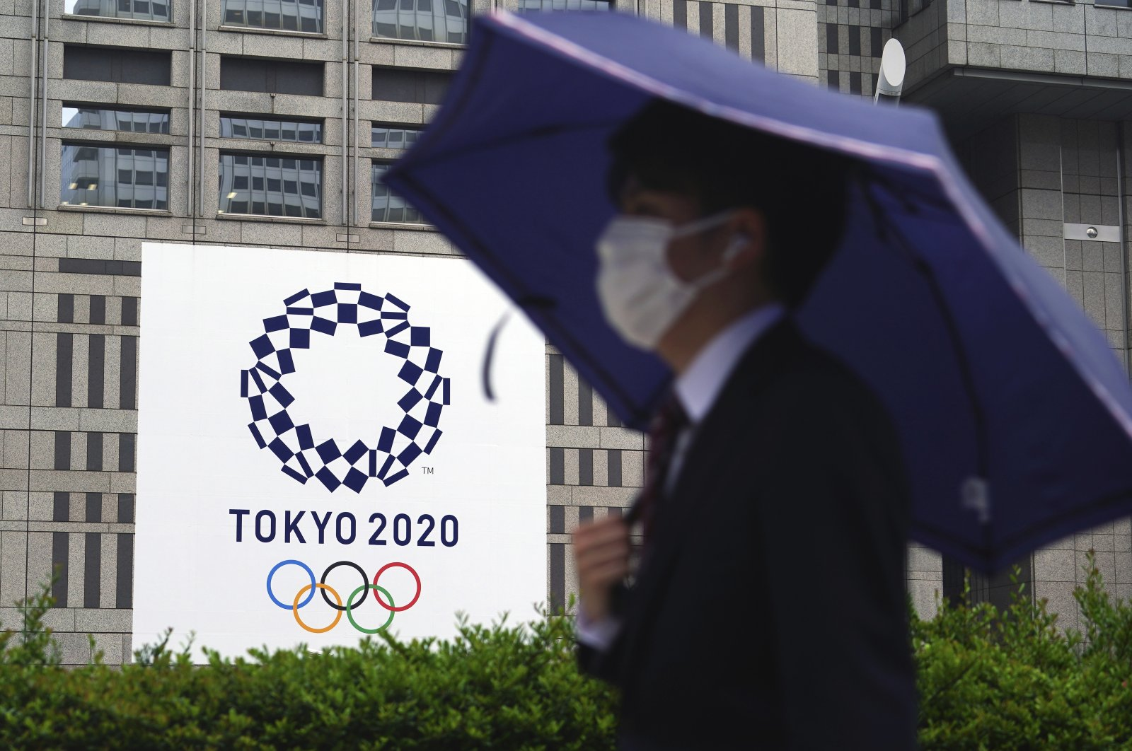 A man wearing a protective mask to help curb the spread of the coronavirus walks in the rain past a banner of the Tokyo 2020 Olympic Games, Tokyo, Japan, May 13, 2021. (AP Photo)
