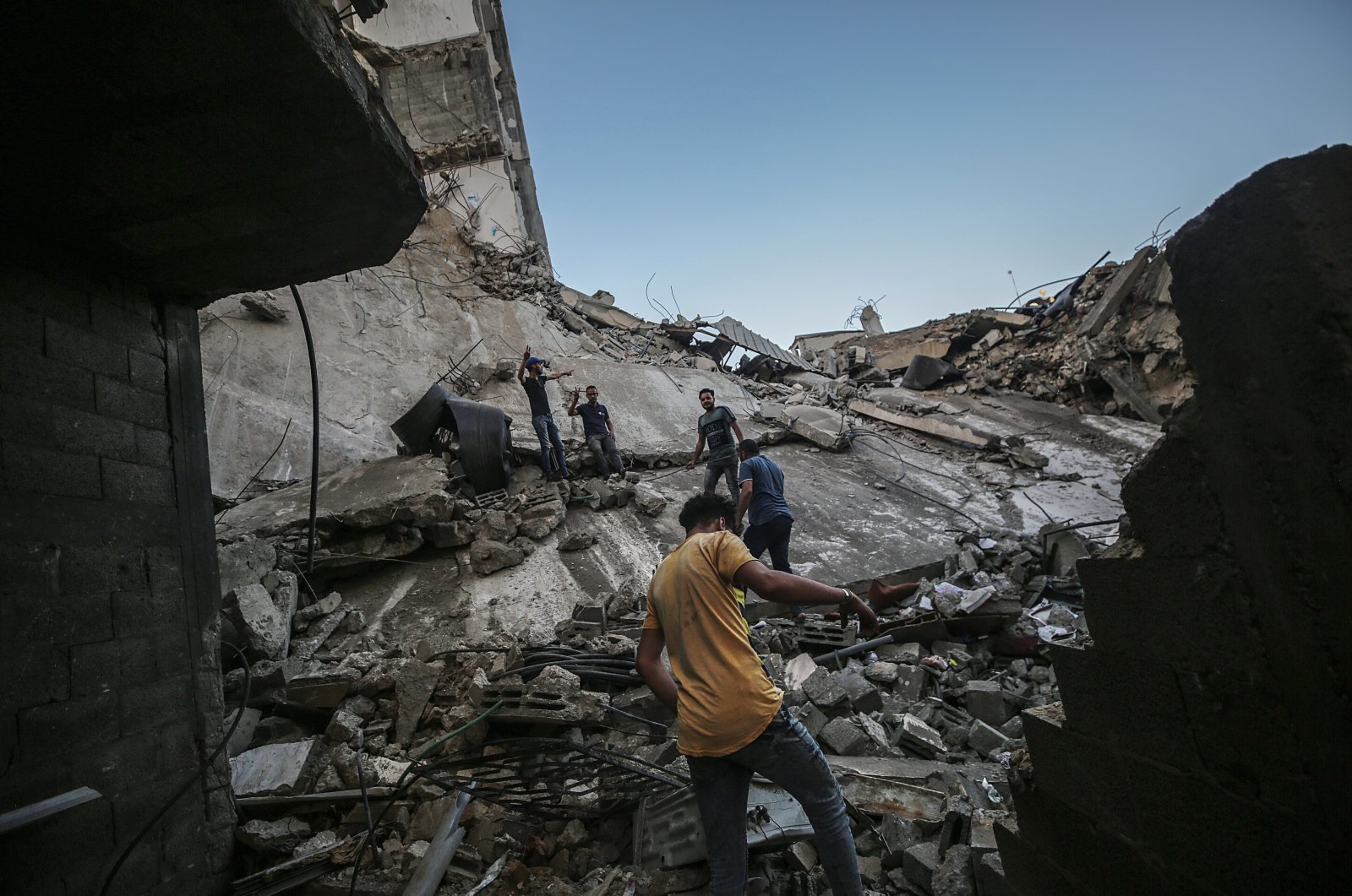 Palestinians inspect the rubble of their destroyed house after Israeli airstrikes, in Gaza City, 19 May 2021. (EPA Photo)