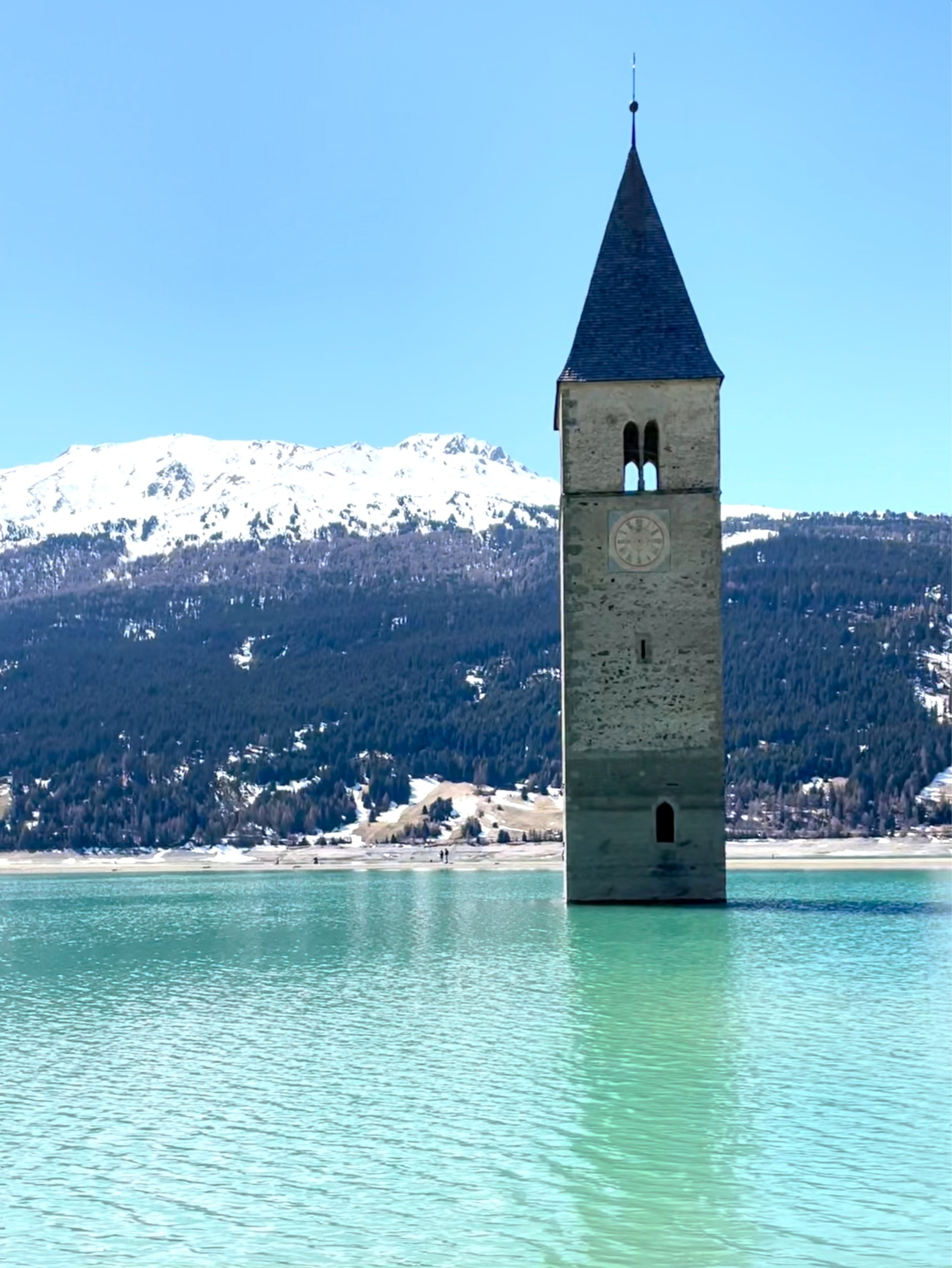 The St. Catherine Church bell tower emerges alone from Lake Reschen as it is drained to repair a hydroelectric plant that replaced the village of Curon 71 years ago, in a screengrab from a video, Resia Lake, Italy, April 24, 2021.  (LUISA AZZOLINI/Handout via Reuters)