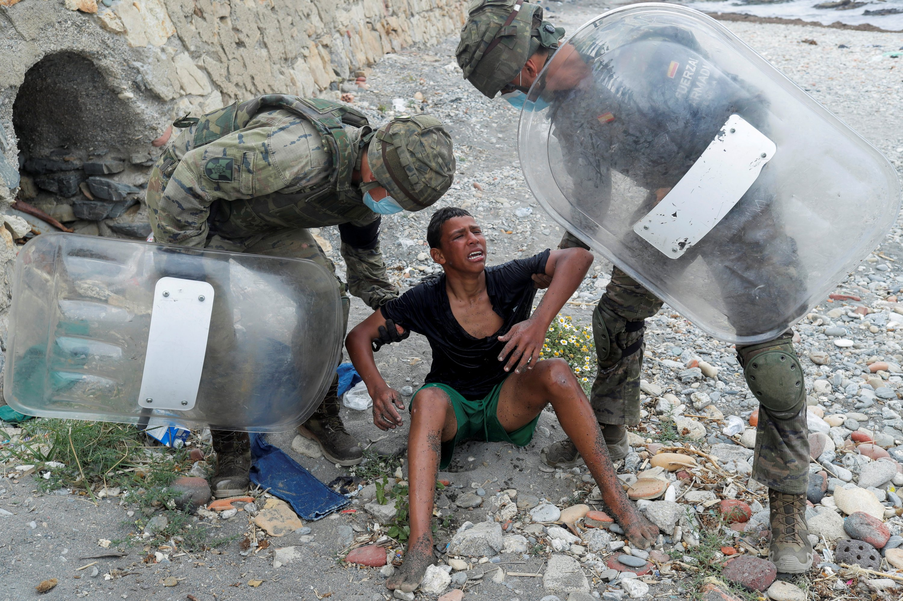 Rashid Mohamed al-Messaoui, 25, a soldier deployed at Spain's North African enclave of Ceuta, assists a Moroccan boy who used empty plastic bottles as a float to swim to Ceuta, on El Tarajal beach, near the fence between the Spanish-Moroccan border, after thousands of migrants swam across the border, in Ceuta, Spain, May 19, 2021. (Reuters Photo)