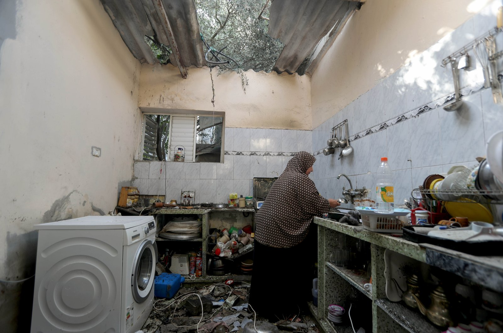 A Palestinian woman works in a kitchen inside a house damaged in an Israeli airstrike, amid Israeli attacks on Gaza, May 20, 2021. (Reuters Photo)