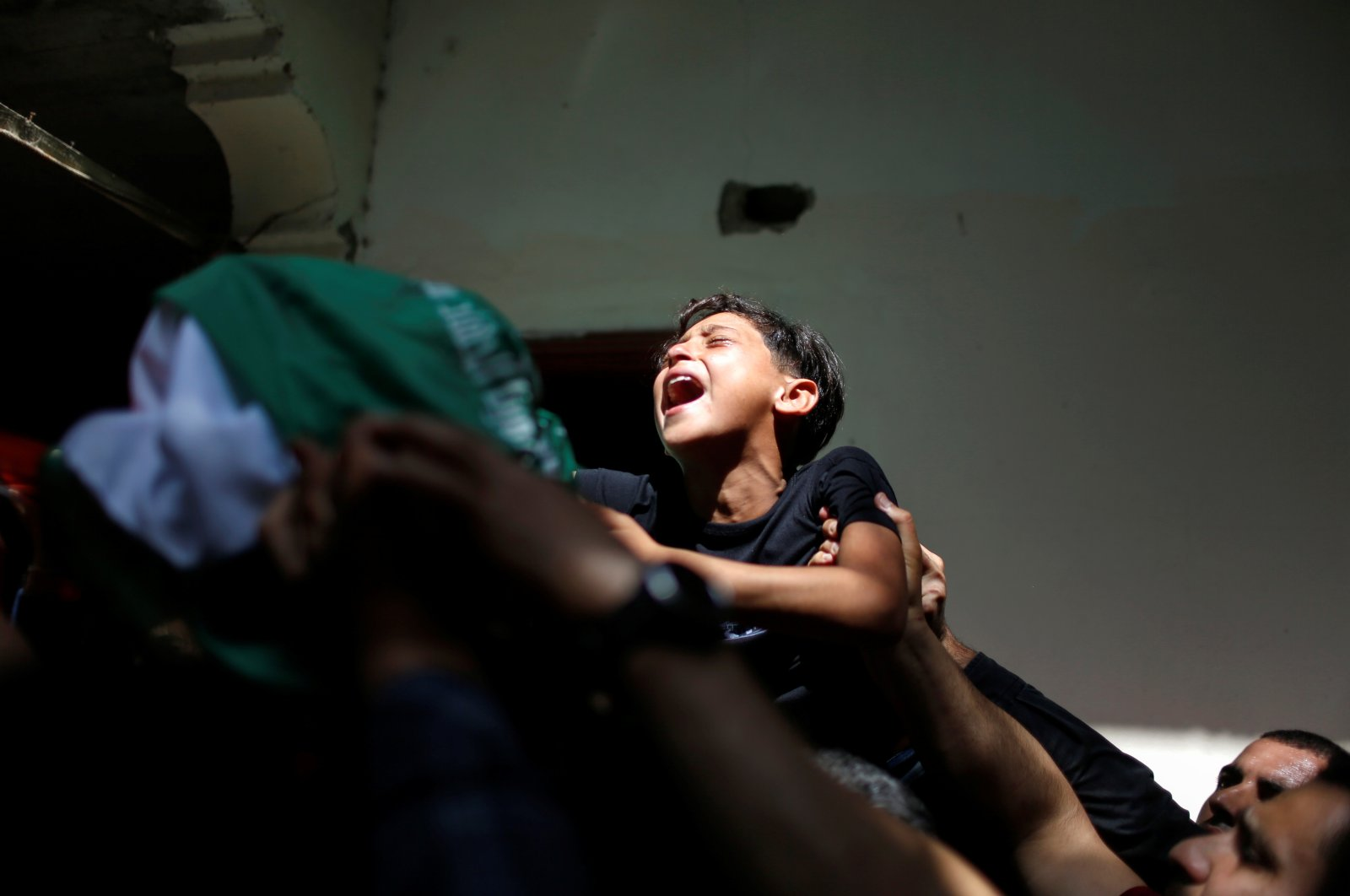 A Palestinian boy cries for his brother Ahmed Al-Shenbari, who was killed by Israeli bombardments, as mourners carry his body during his funeral in the northern Gaza Strip, Palestine, May 11, 2021. (Reuters Photo)