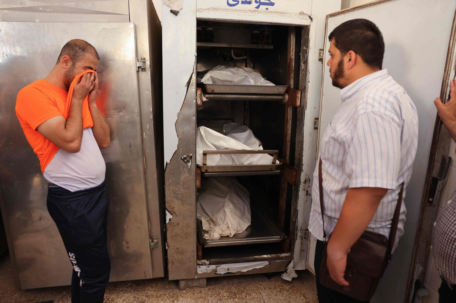 A brother weeps in front of the corpses at the morgue, where Iyad, a 33-year-old wheelchair-bound Palestinian man killed in his house along with his pregnant wife and their 3-year-old daughter during an Israeli airstrike, were trasported, Deir el-Balah, Gaza Strip, Palestine. (AFP Photo)