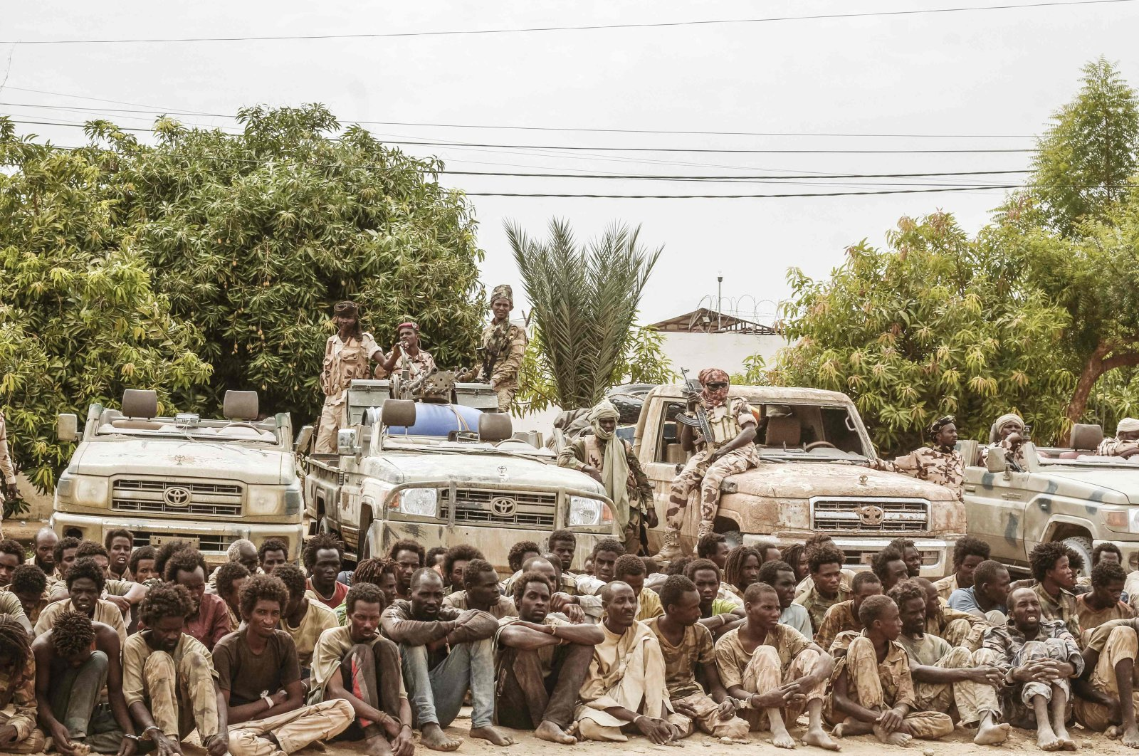 A group of captured rebels from the Front for Change and Concord in Chad (FACT) pose with their confiscated weapons and vehicles at the headquarters of the Chadian Army in N'Djamena, Chad, Central Africa, May 9, 2021. (AFP Photo)