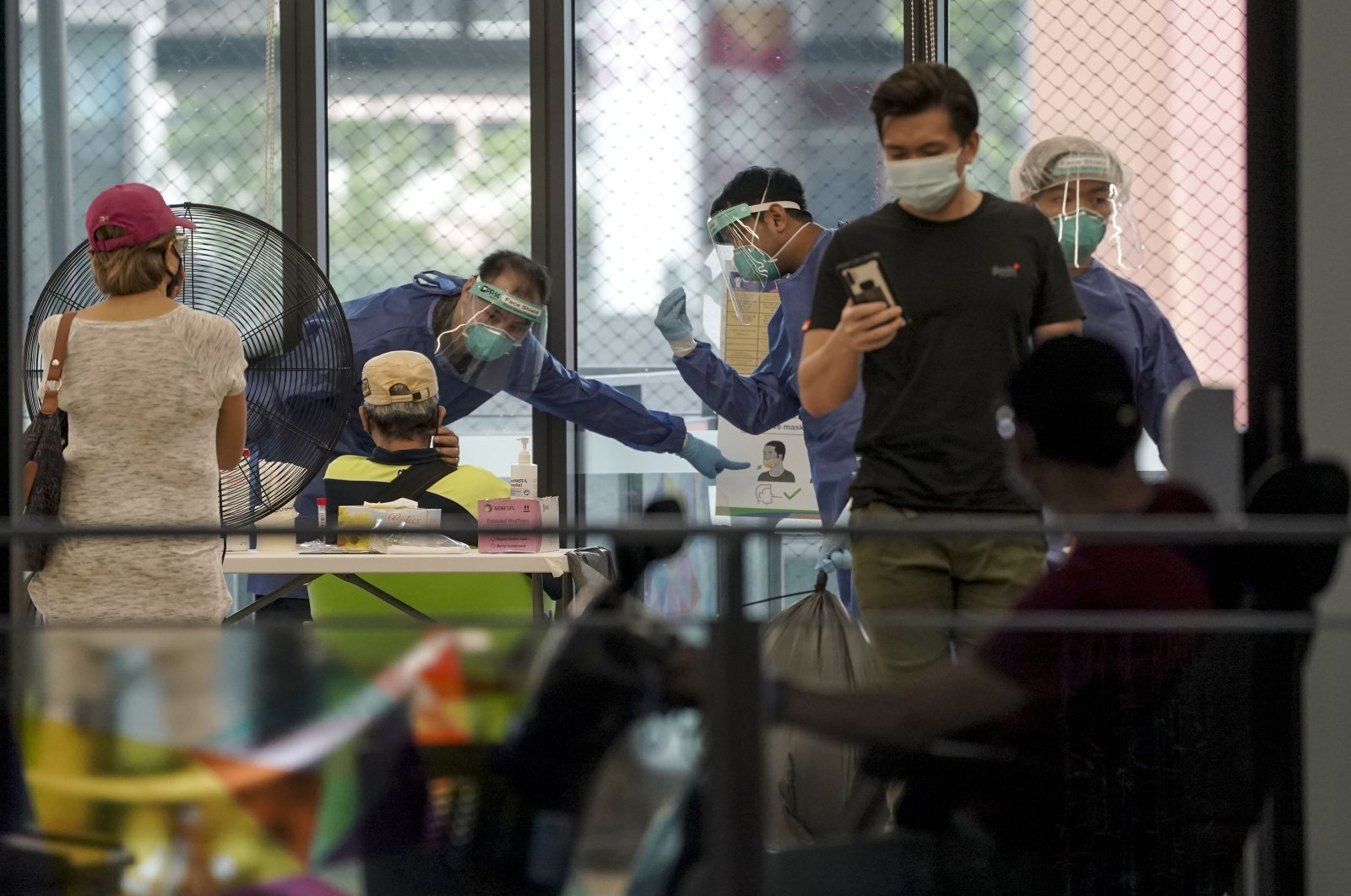 Medical personnel wearing PPE inside a swab testing station at the One Tampines Hub in Singapore, May 20, 2021. (EPA Photo)