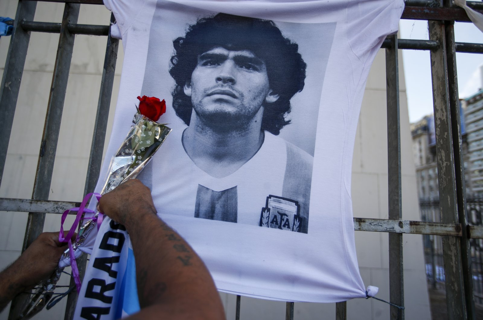 A man places a flower on a jersey with the face of late footballing icon Diego Maradona during a march to demand answers regarding his death, in Buenos Aires, Argentina, March 10, 2021. (AP Photo)