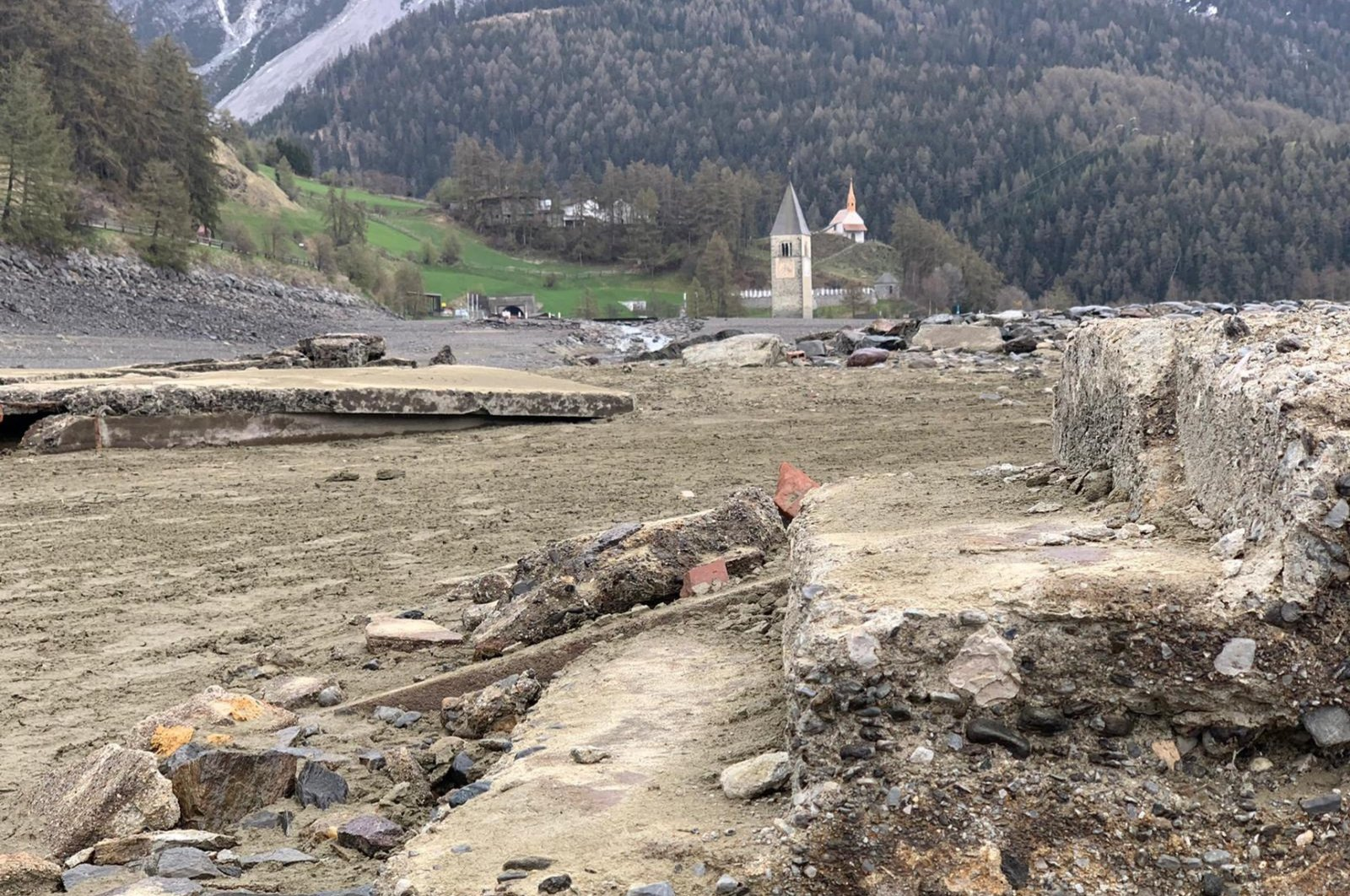 The famous St. Catherine Church bell tower stands in the drained Lake Reschen, Resia, Italy, May 14, 2021. (EPA/G.News Photo)