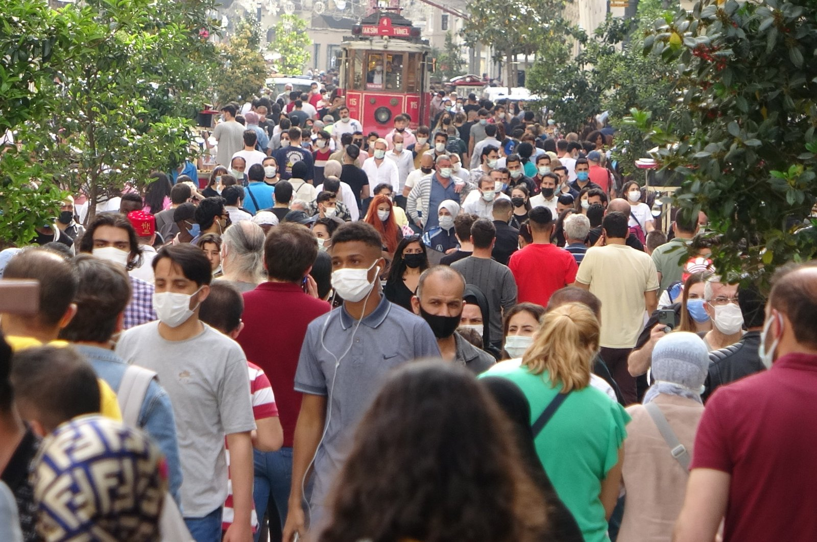 People with face masks walk on Istiklal Street near Istanbul's famous Taksim square after a 17-day total lockdown across Turkey, May 17, 2021. (IHA Photo)